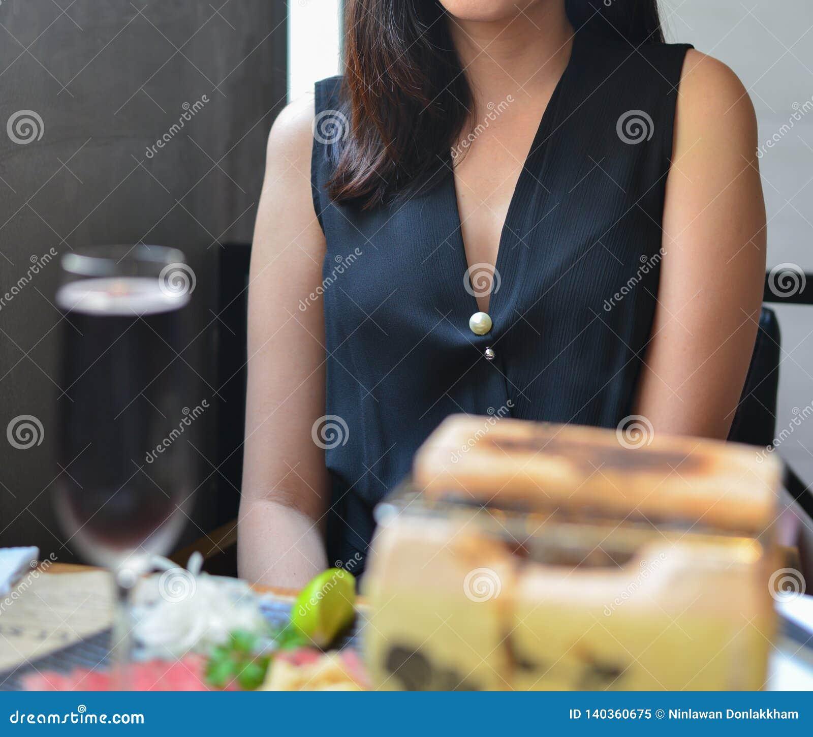Jovem mulher elegante que senta-se no restaurante