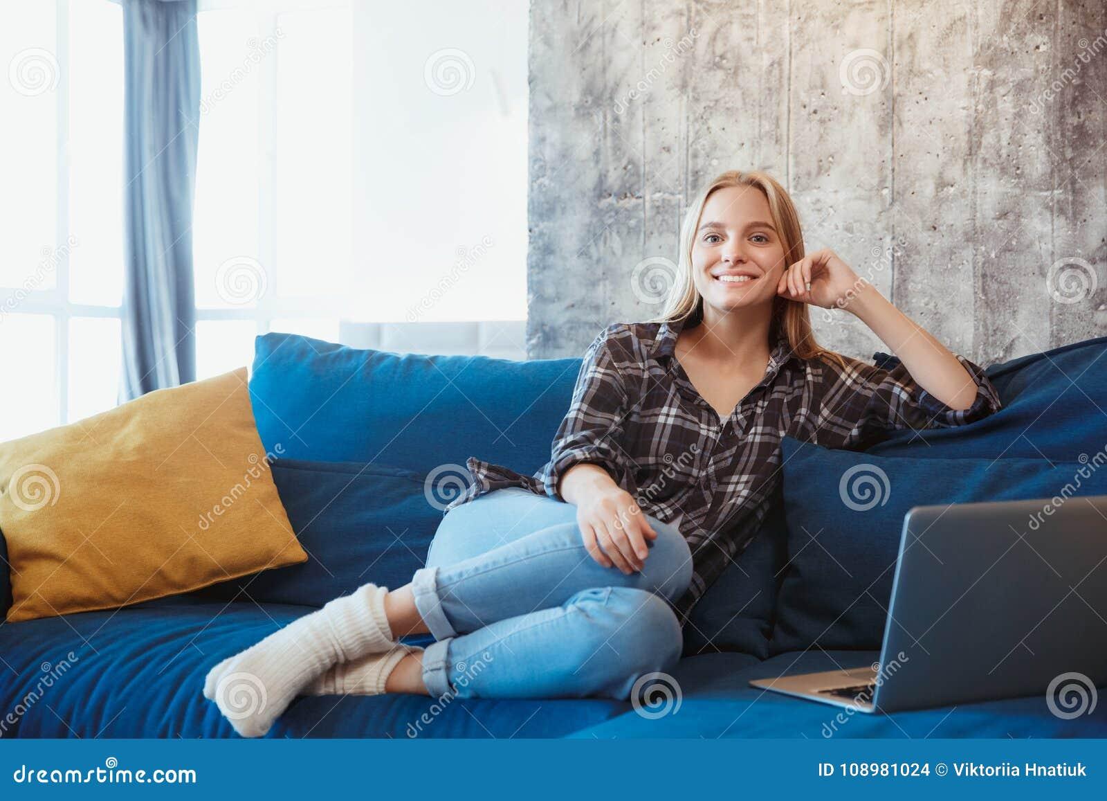 Jovem mulher em casa na sala de visitas que descansa no treinador