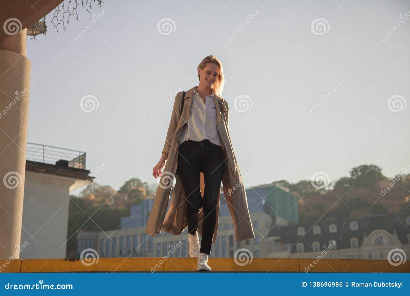 Jovem mulher em um revestimento à moda da mola em vidros elegantes em um t-shirt branco em uma bolsa de couro preta que anda avan