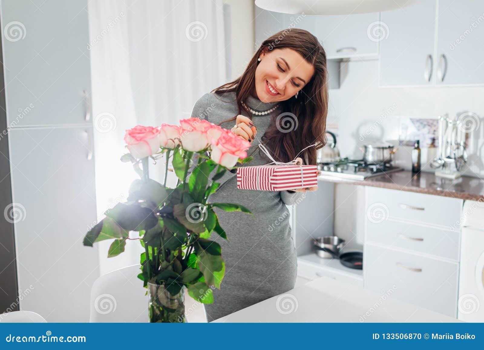 A jovem mulher encontrou a caixa de presente e o ramalhete das rosas na cozinha Presente de sorriso feliz da abertura da menina