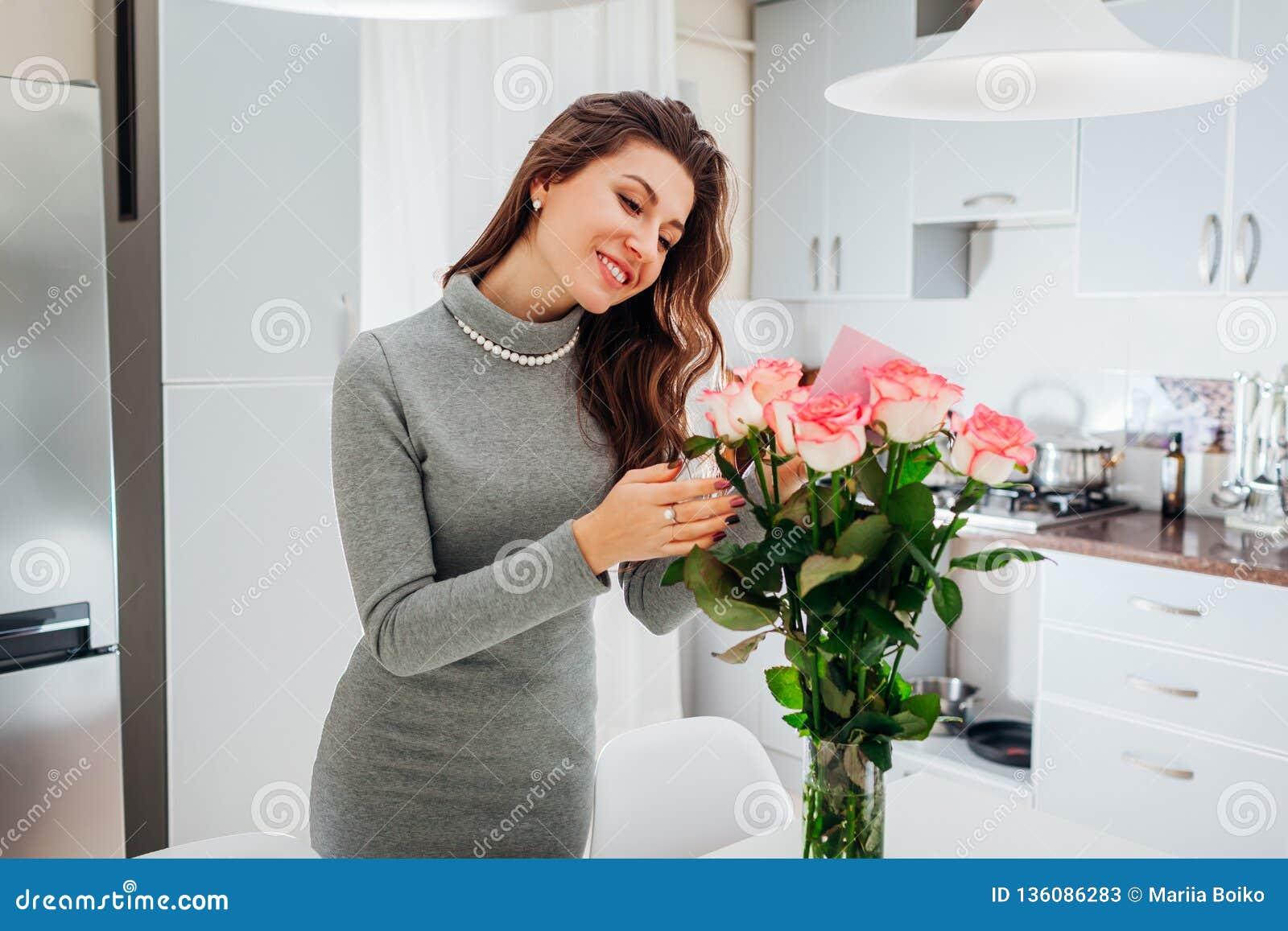 A jovem mulher encontrou o ramalhete das rosas com o cartão na cozinha Nota feliz da leitura da menina nas flores Rosa vermelha