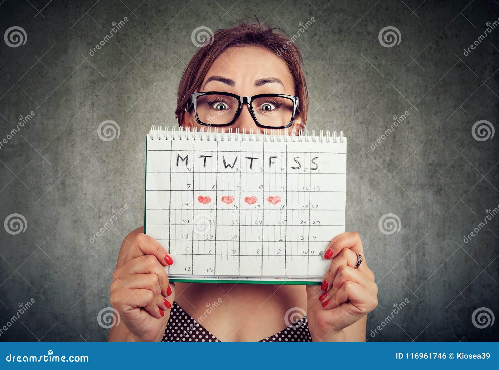 Jovem mulher engraçada nos vidros que escondem atrás de um calendário dos períodos e que olham a câmera