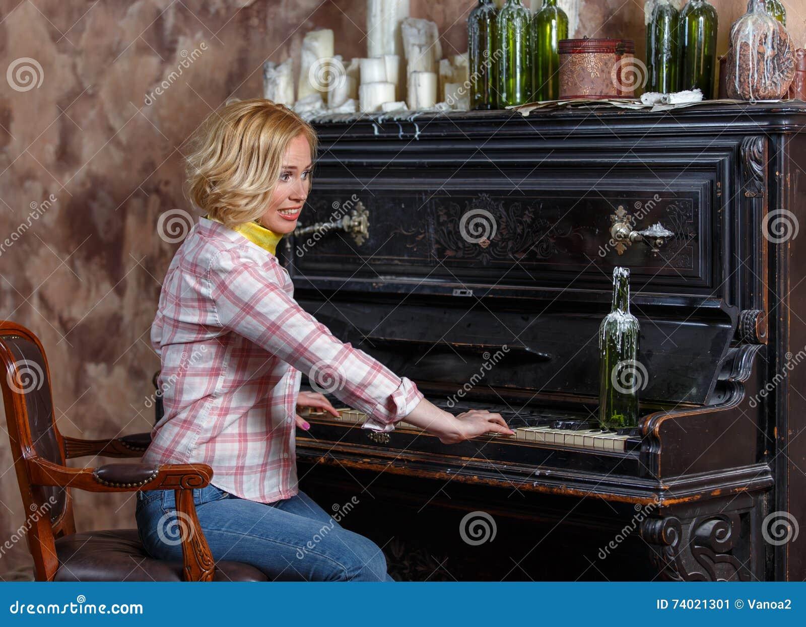Jovem mulher engraçada que joga o piano retro gasto