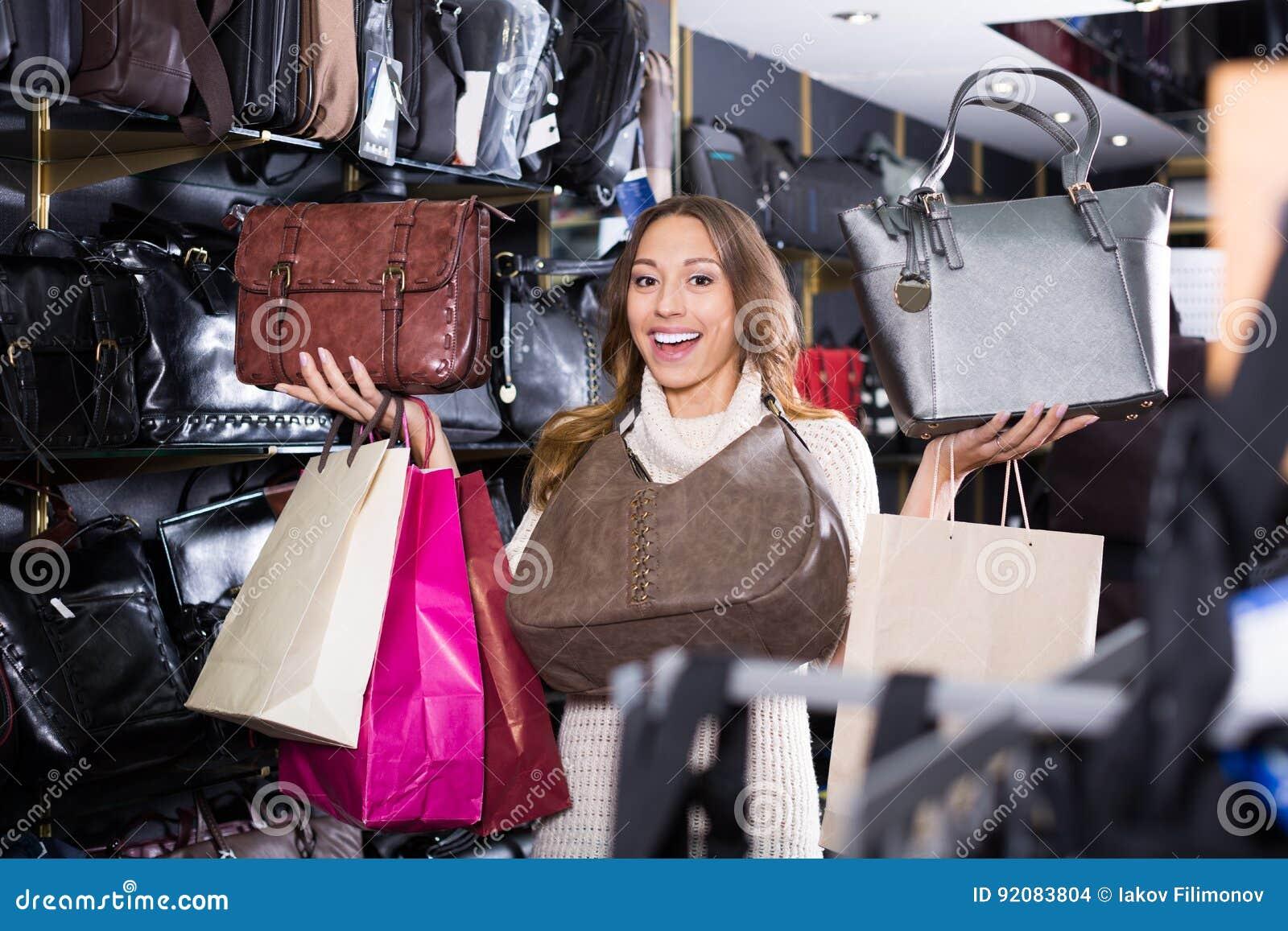 Jovem mulher entusiasmado que seleciona a bolsa nova