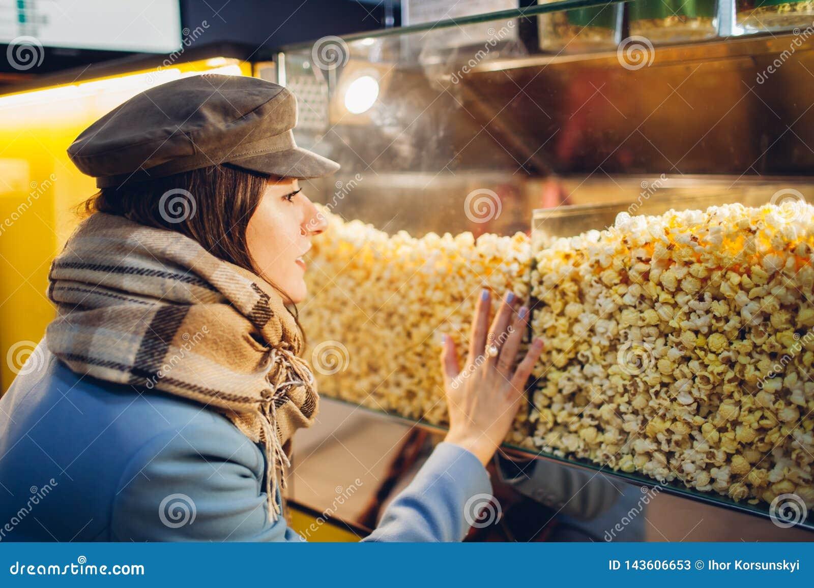 A jovem mulher escolhe a pipoca no cinema Alimento e petiscos