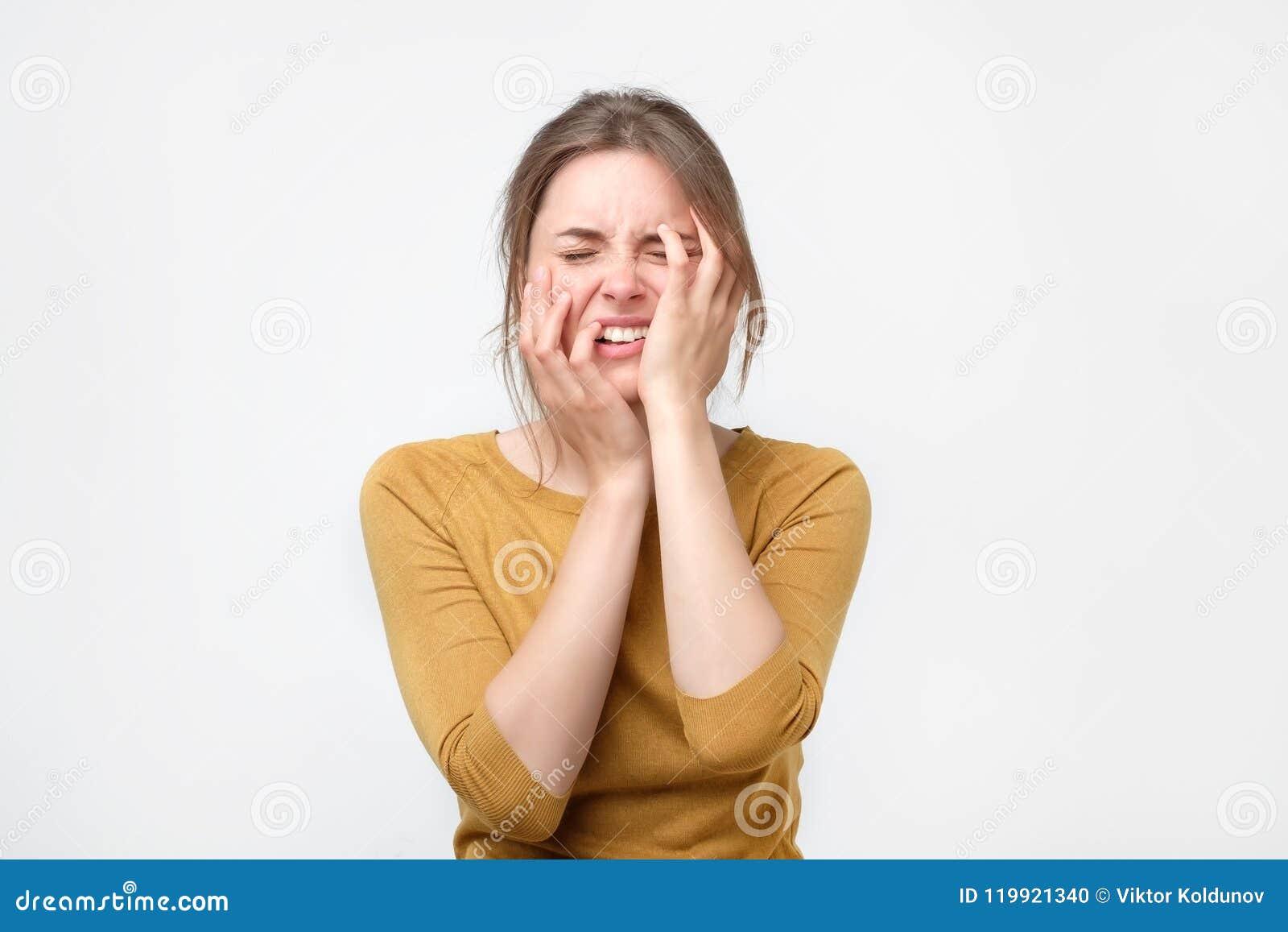 Jovem mulher esgotada na camiseta amarela que toca em sua cabeça com os olhos fechados