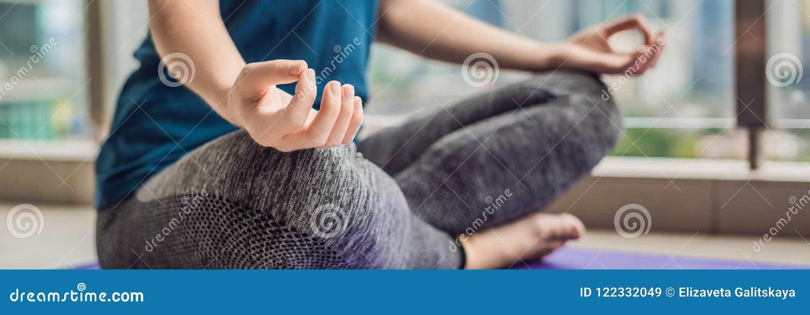 A jovem mulher está praticando a ioga na manhã em seu balcão com uma vista panorâmica da cidade e da BANDEIRA dos arranha-céus, f