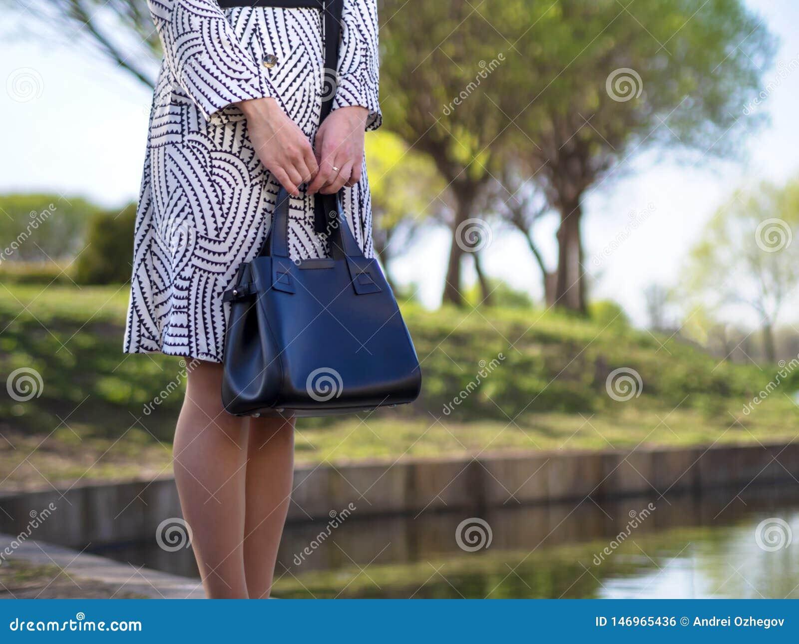 Jovem mulher europeia à moda em uma capa de chuva, calças justas, sapatas com saltos, com um saco de couro preto em suas mãos em