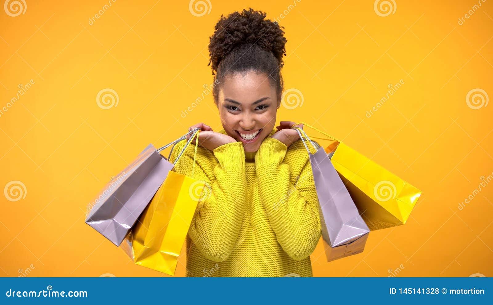 Jovem mulher excitada na camiseta amarela ? moda que guarda sacos de compras, desconto