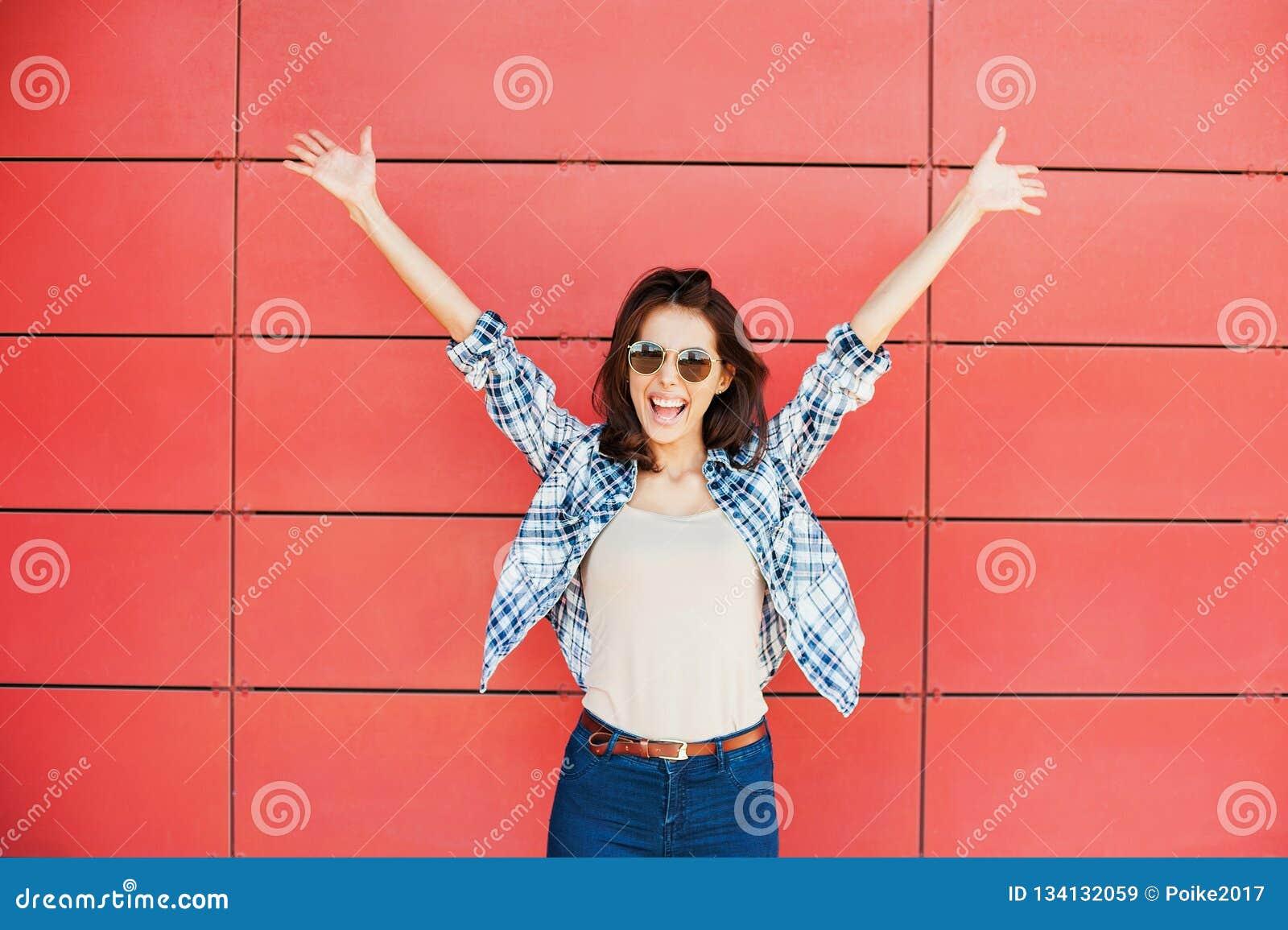 Jovem mulher feliz alegre que salta contra a parede vermelha Retrato bonito entusiasmado da menina