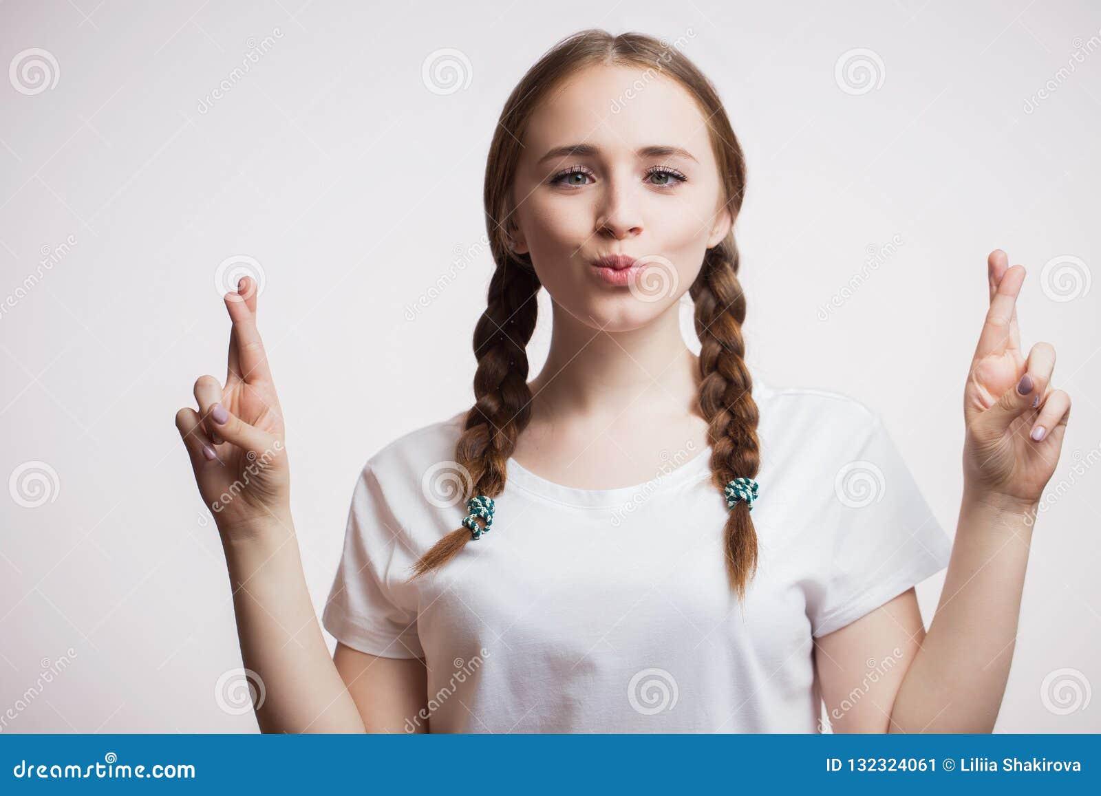 A jovem mulher feliz alegre que veste vidros e um t-shirt faz uma careta engraçada, cruza seus dedos no fundo branco humano