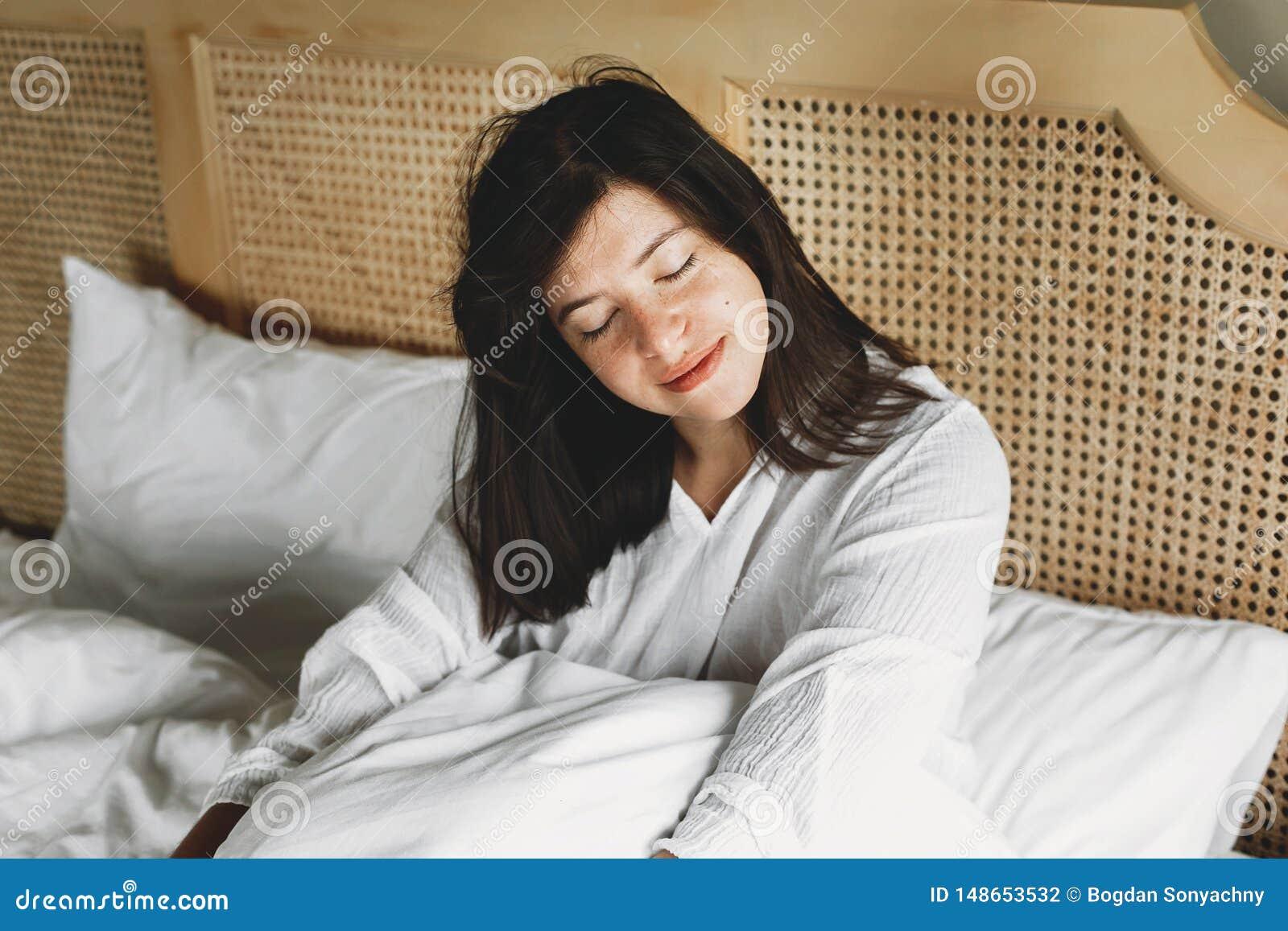 Jovem mulher feliz bonita que encontra-se na cama na manh? na sala de hotel ou no quarto da casa Menina moreno ? moda no relaxame