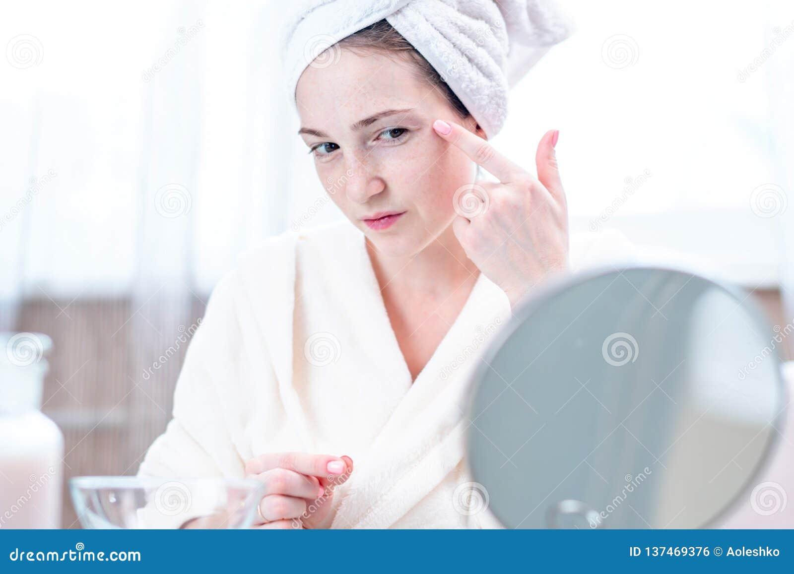 Jovem mulher feliz bonita que olha sua pele em um espelho Conceito da higiene e do cuidado oportunos para a pele