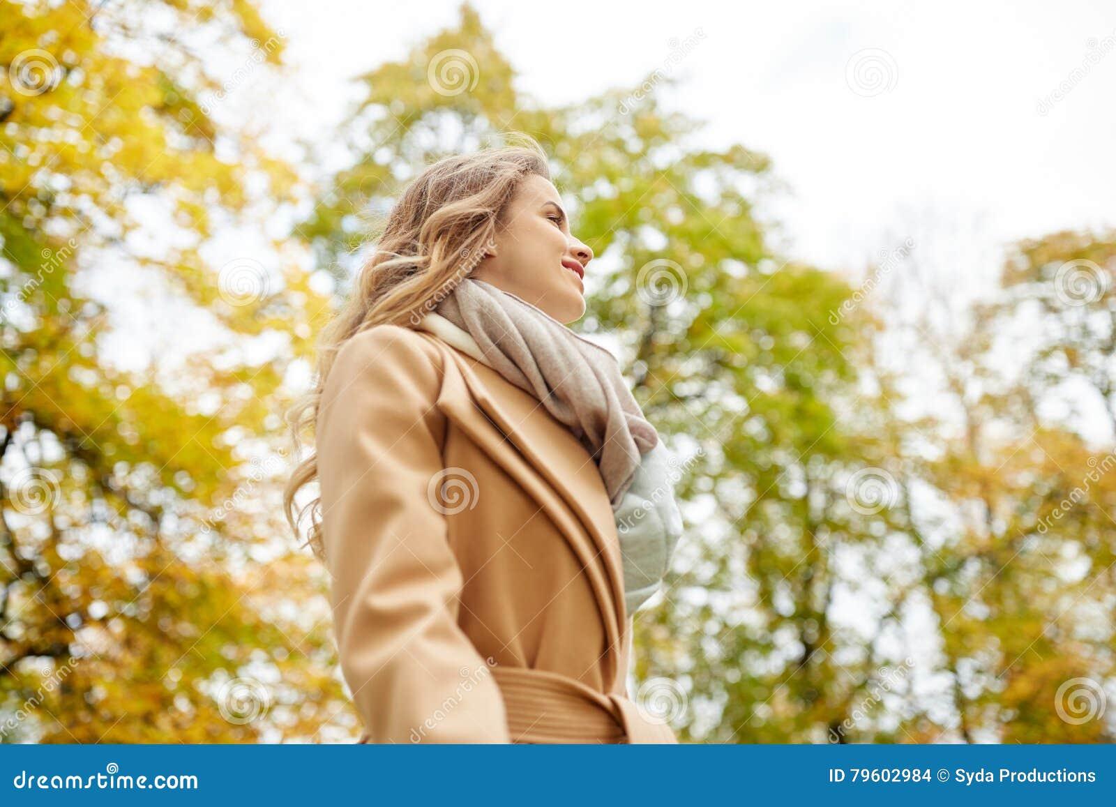 Jovem mulher feliz bonita que sorri no parque do outono