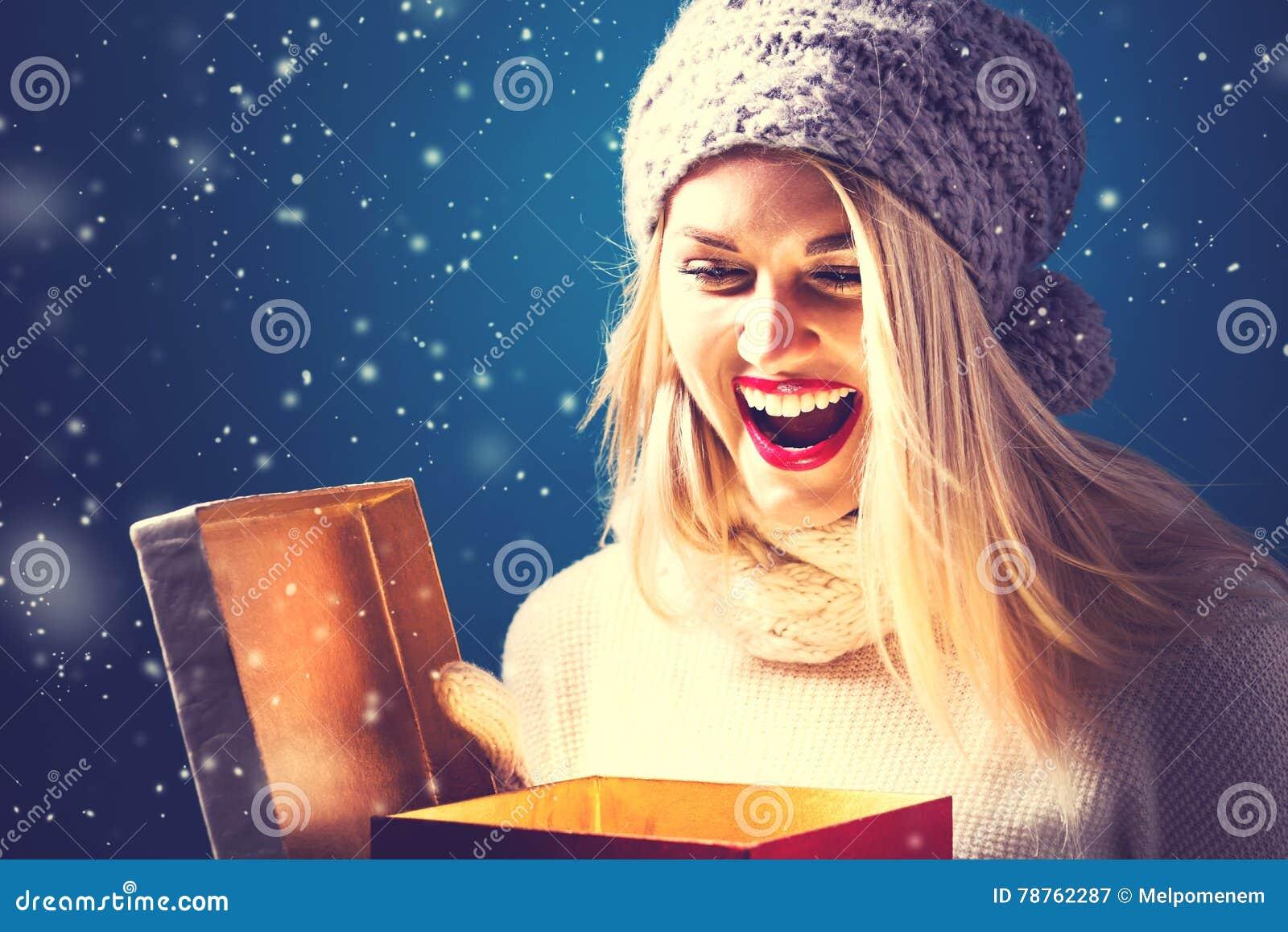Jovem mulher feliz com a caixa do presente de Natal