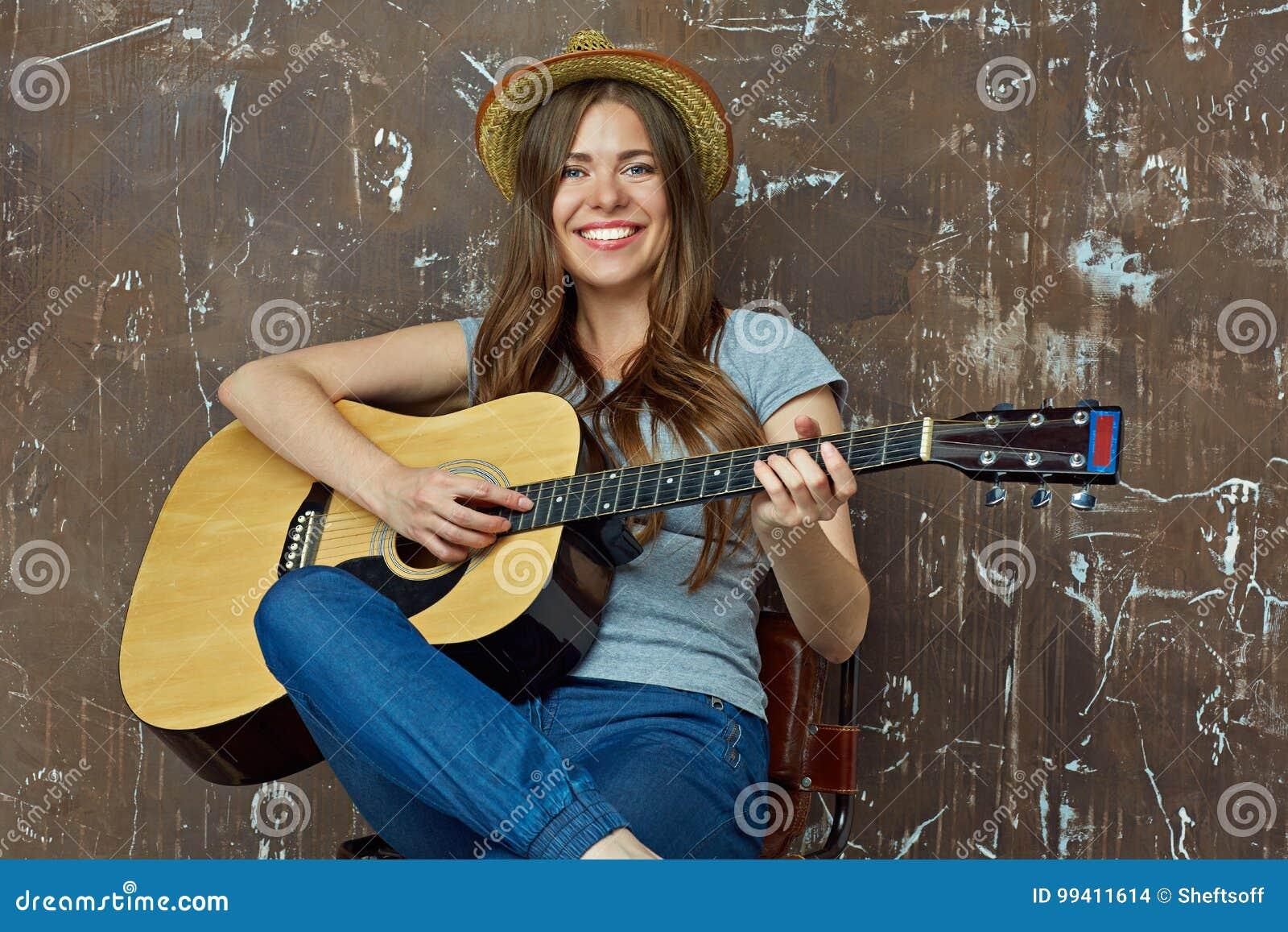 Jovem mulher feliz com o chapéu que senta-se com a guitarra acústica no grung