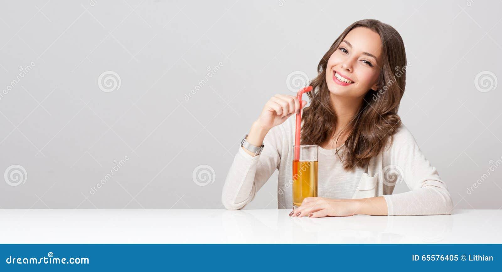 Jovem mulher feliz com vidro do suco de fruto