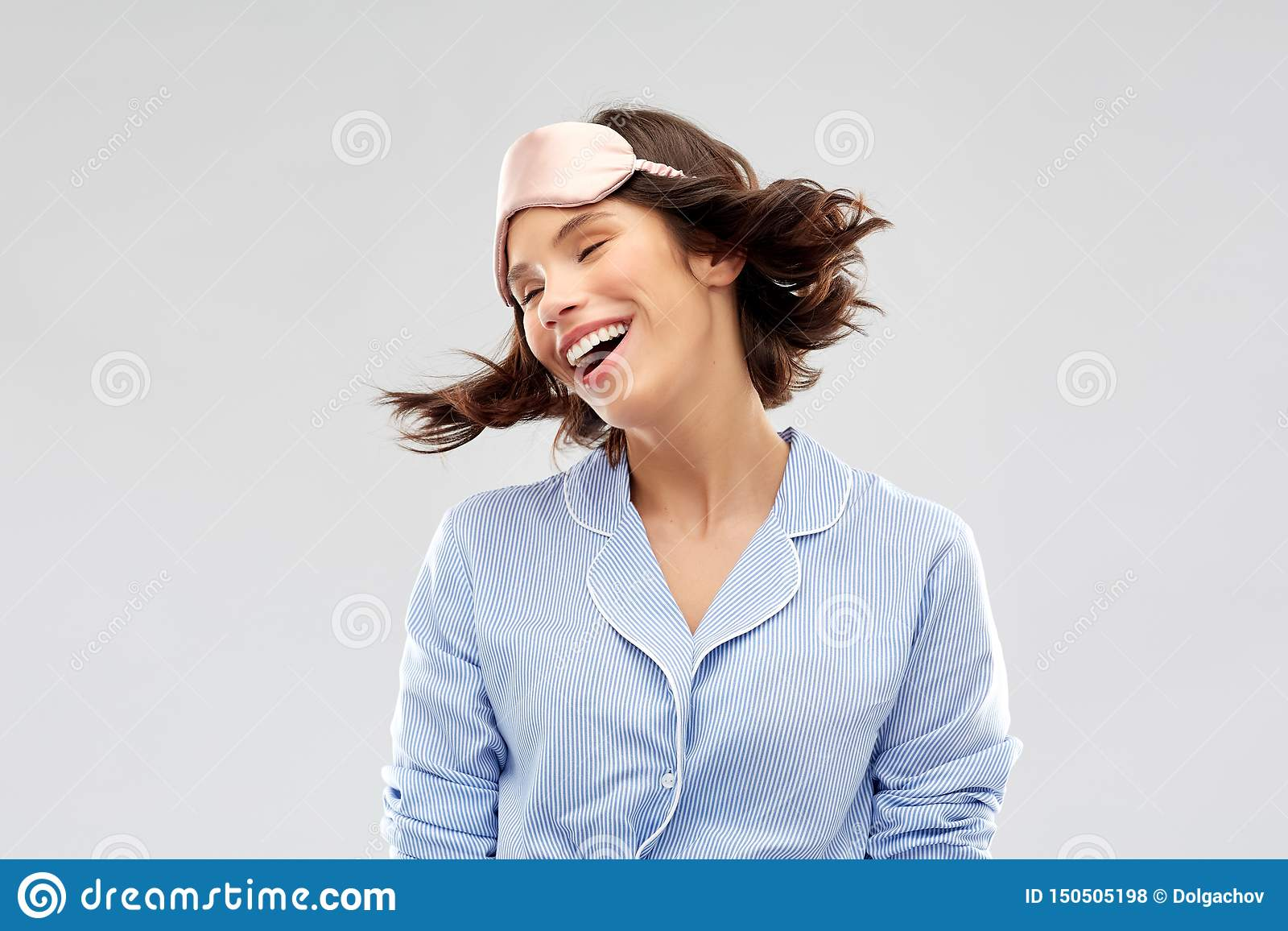 Jovem mulher feliz na m?scara do sono do pijama e do olho