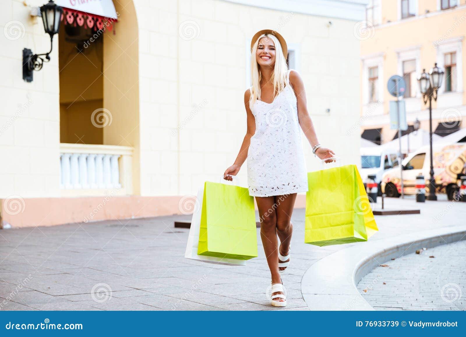 Jovem mulher feliz no chapéu que guarda sacos de compras ao andar