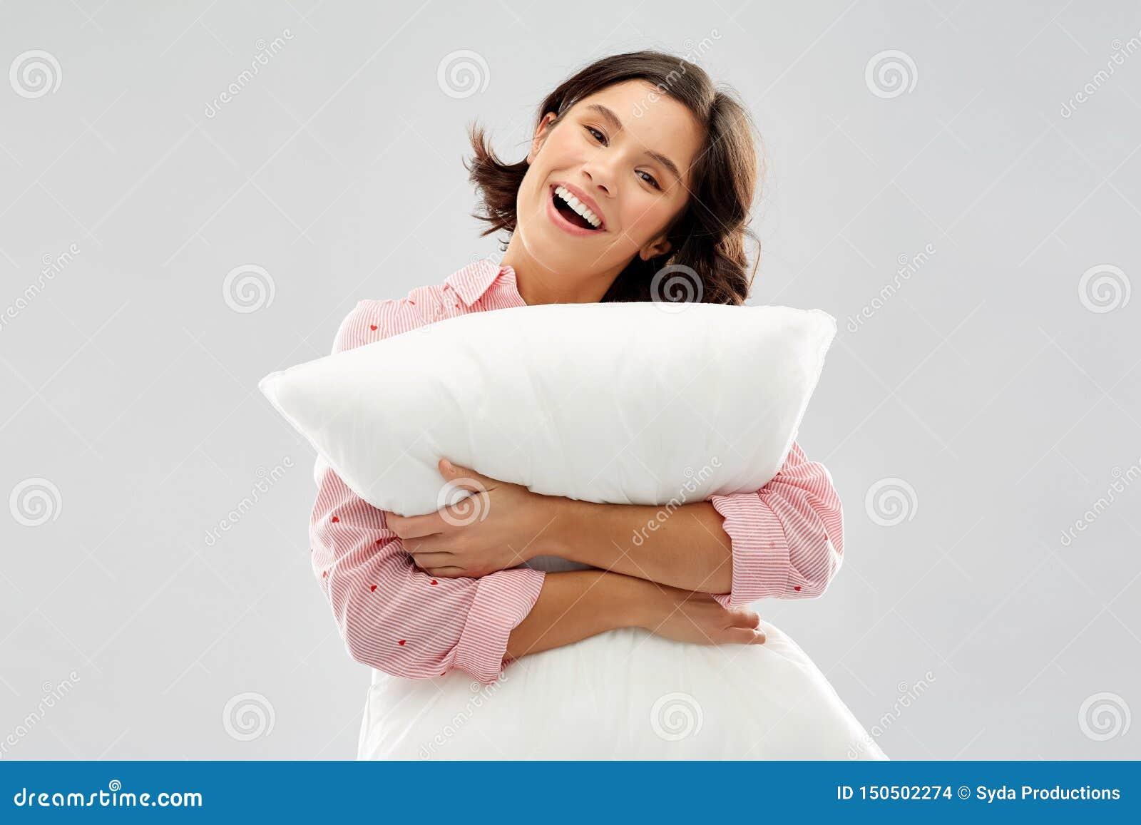 Jovem mulher feliz no pijama que abra?a o descanso