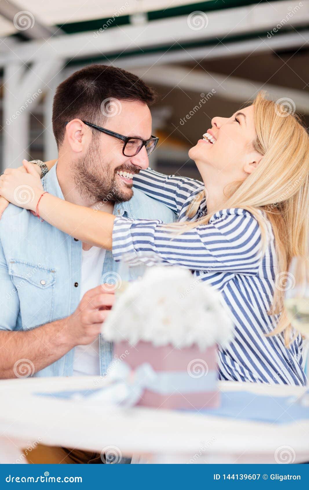 Jovem mulher feliz que abraça seu noivo após ter aceitado sua proposta de união
