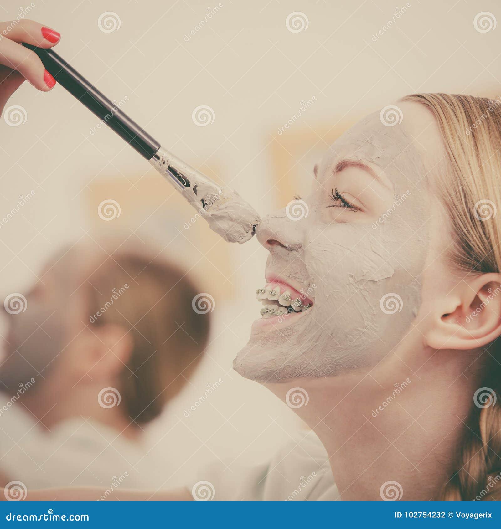 Jovem mulher feliz que aplica a máscara da lama no nariz