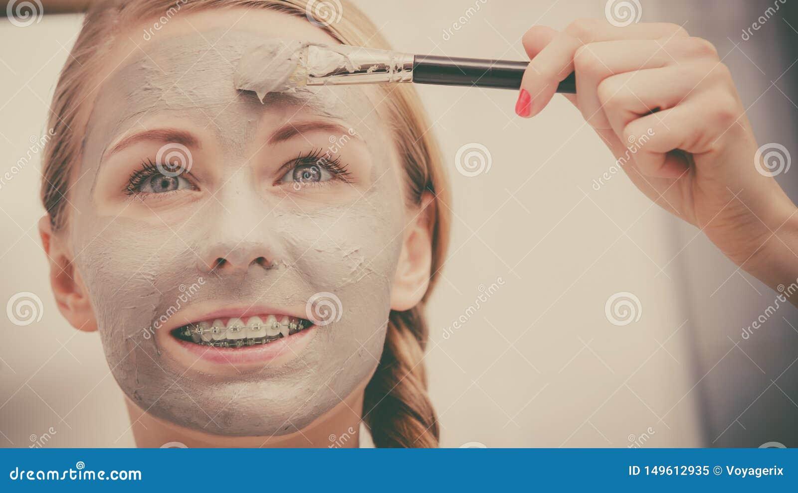 Jovem mulher feliz que aplica a m?scara da lama na cara
