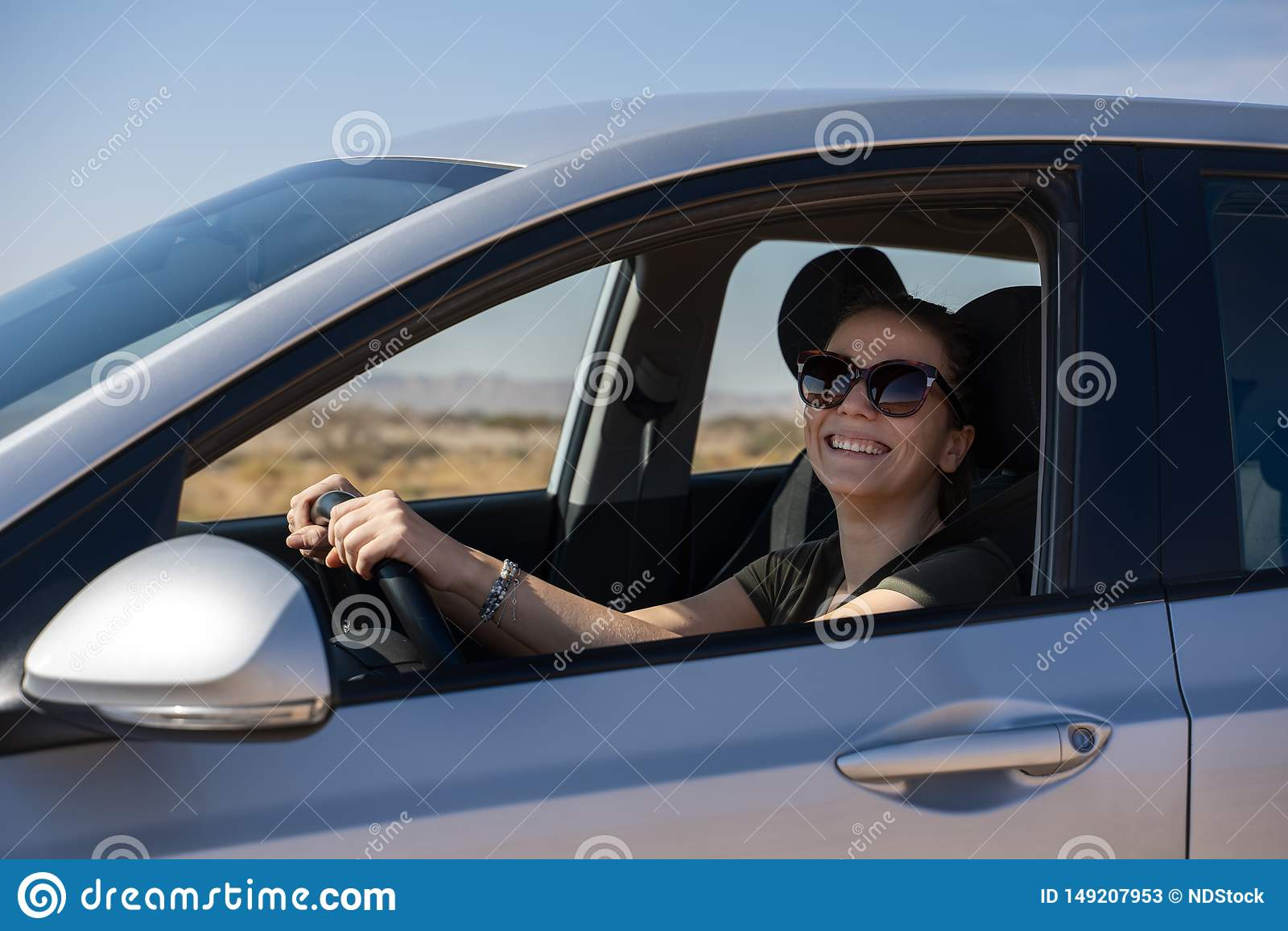Jovem mulher feliz que conduz um carro alugado no deserto de Israel