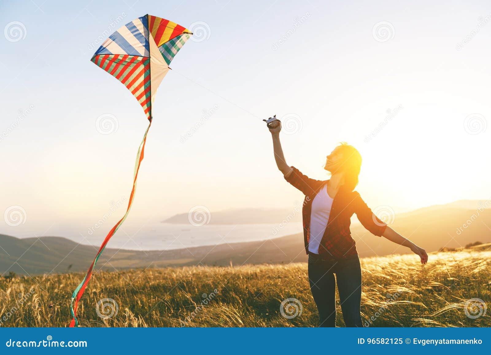 Jovem mulher feliz que corre com o papagaio na clareira no por do sol no verão