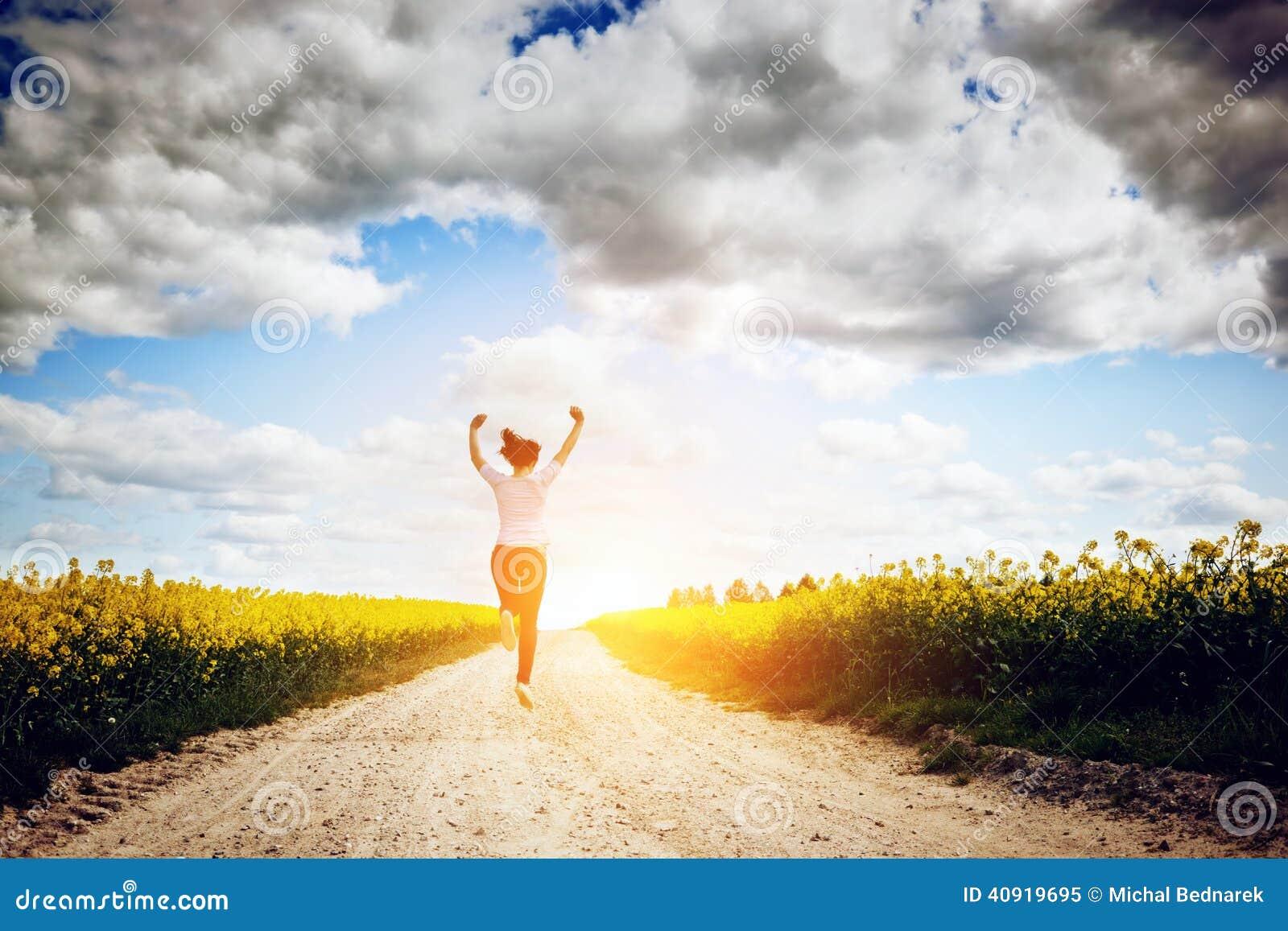 Jovem mulher feliz que corre e que salta para a alegria