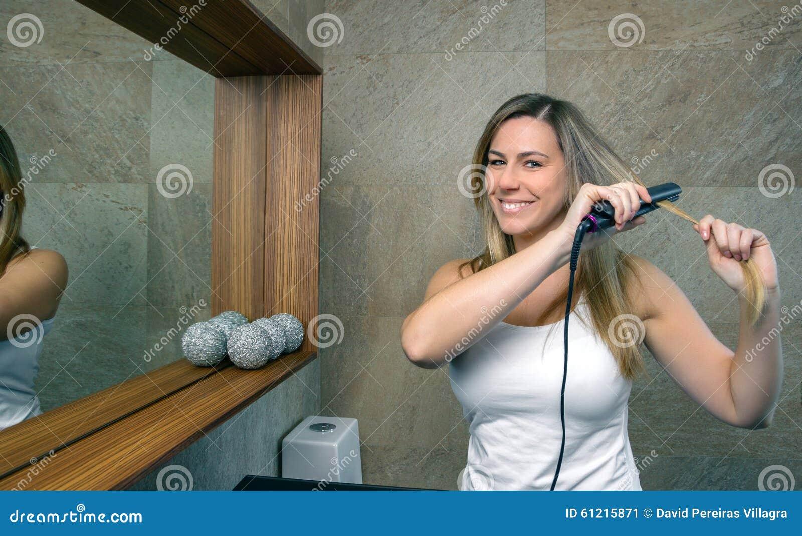 Jovem mulher feliz que endireita o cabelo com a