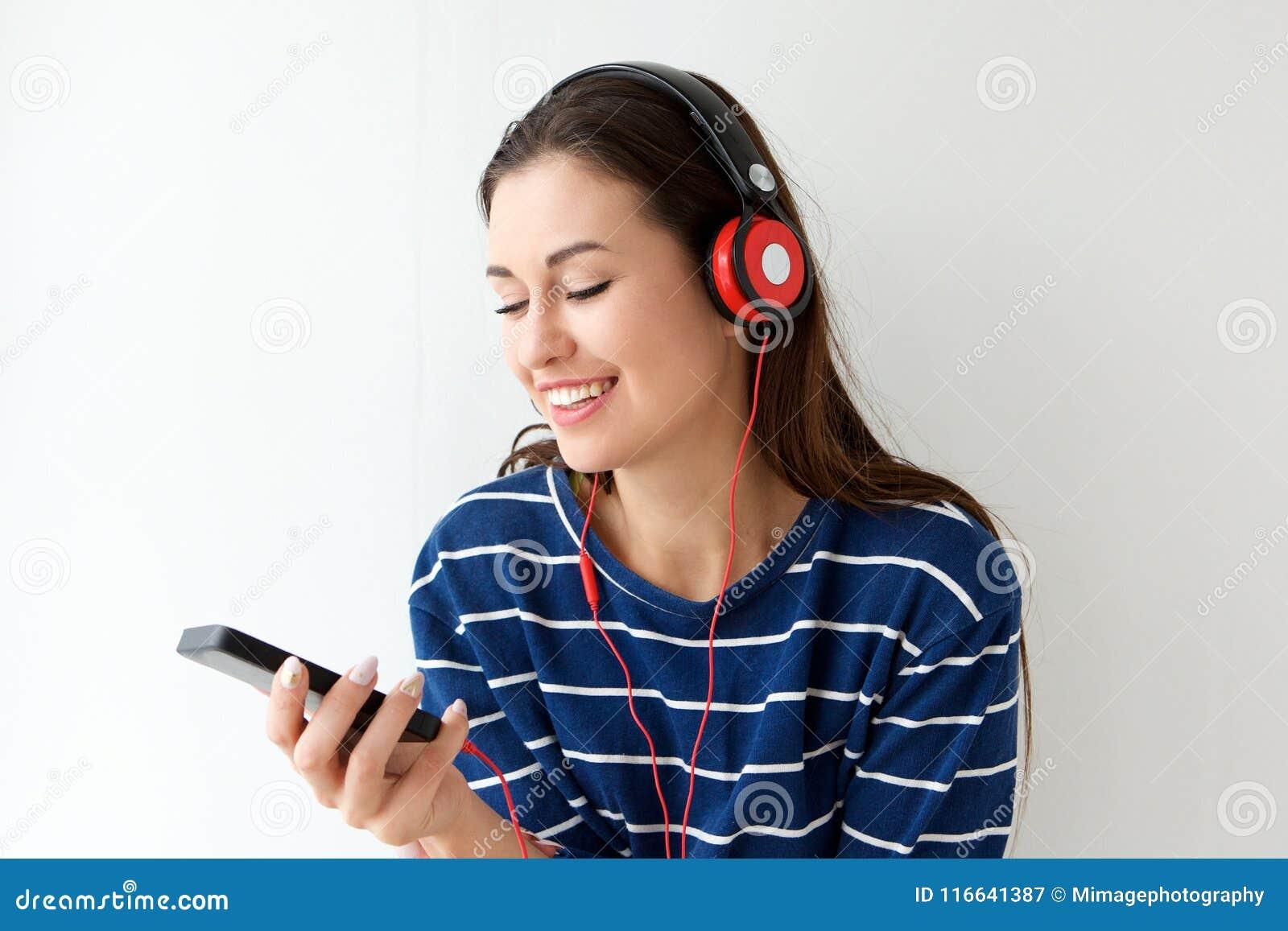 Jovem mulher feliz que olha o telefone celular e que escuta a música com fones de ouvido