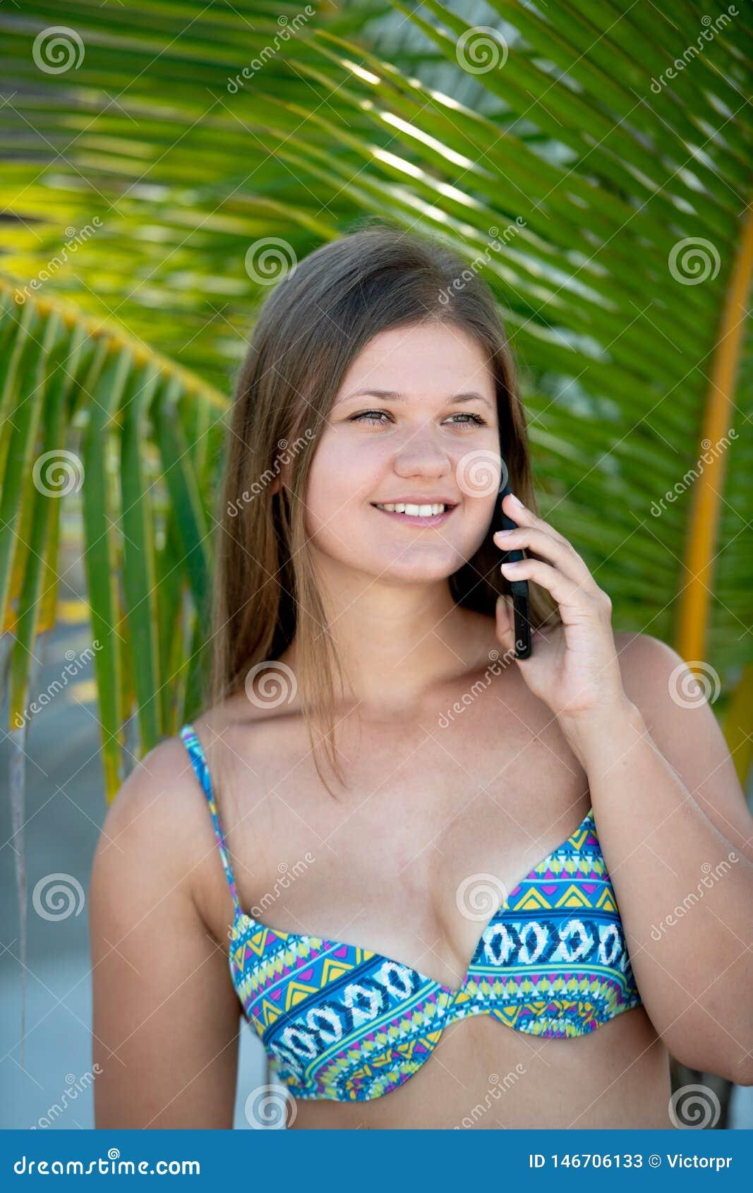 Jovem mulher feliz sob a palmeira que fala no telefone esperto