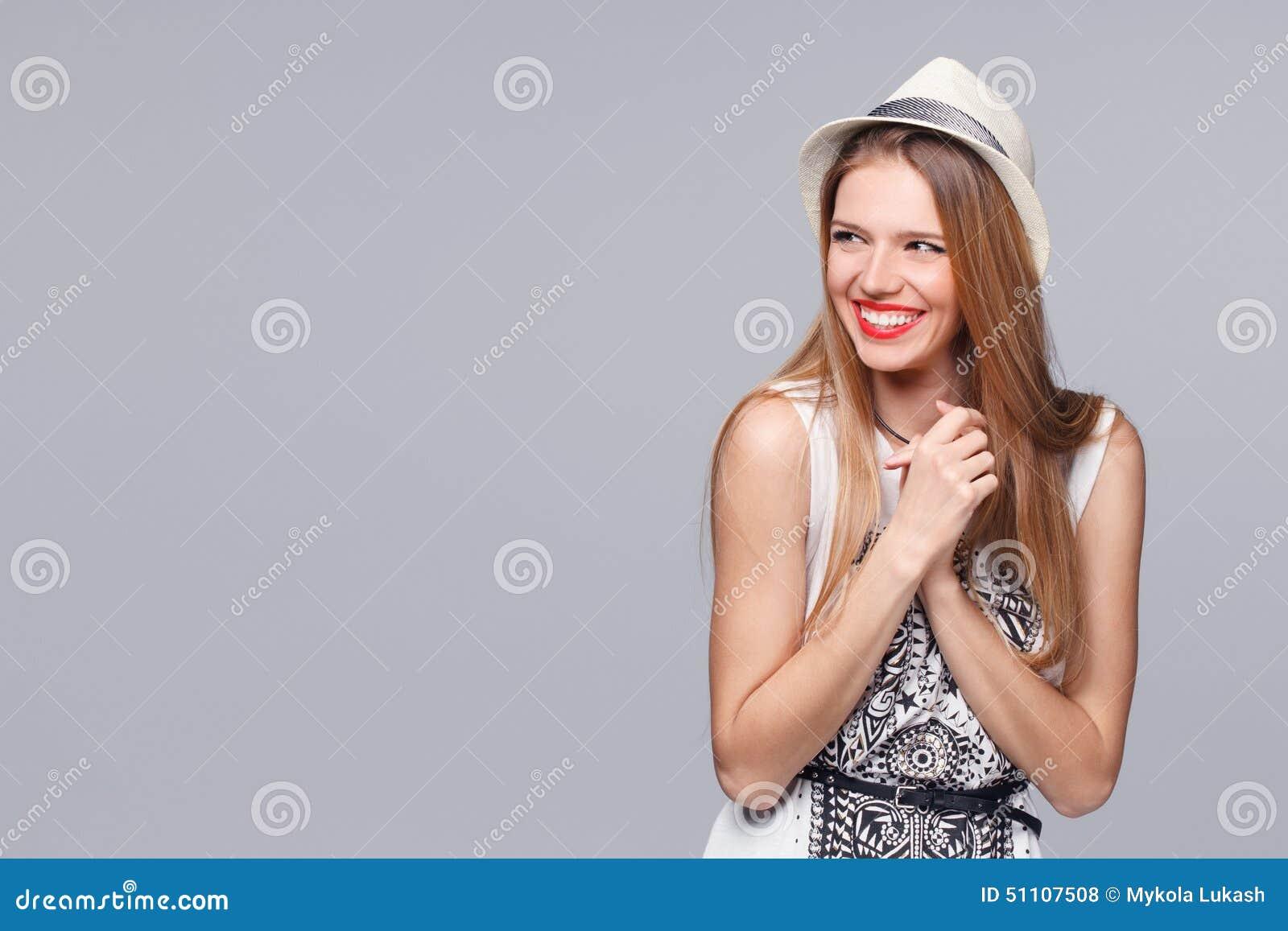 Jovem mulher feliz surpreendida que olha lateralmente no excitamento Isolado sobre o cinza