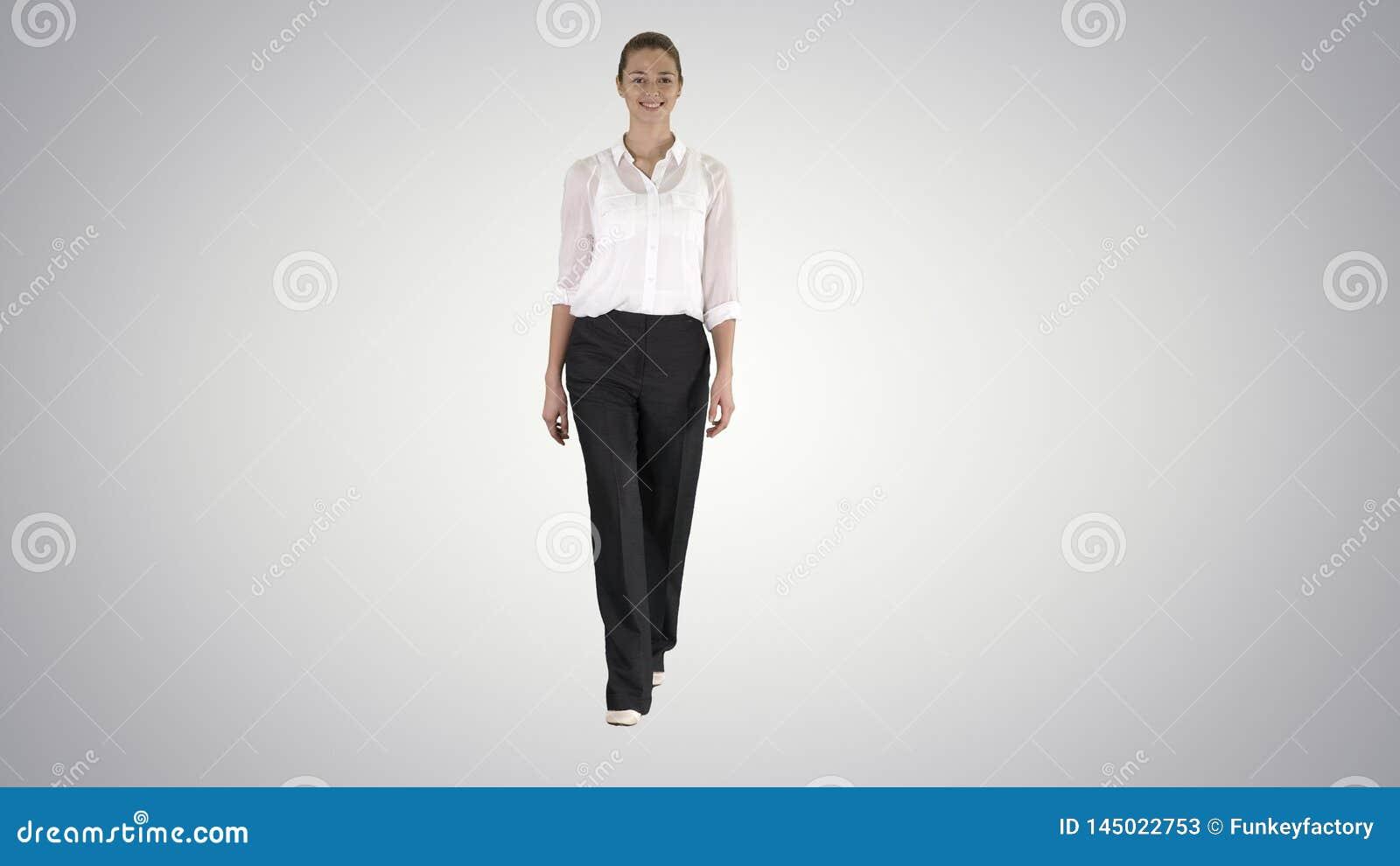 Jovem mulher formal que anda e que sorri no fundo do inclina??o