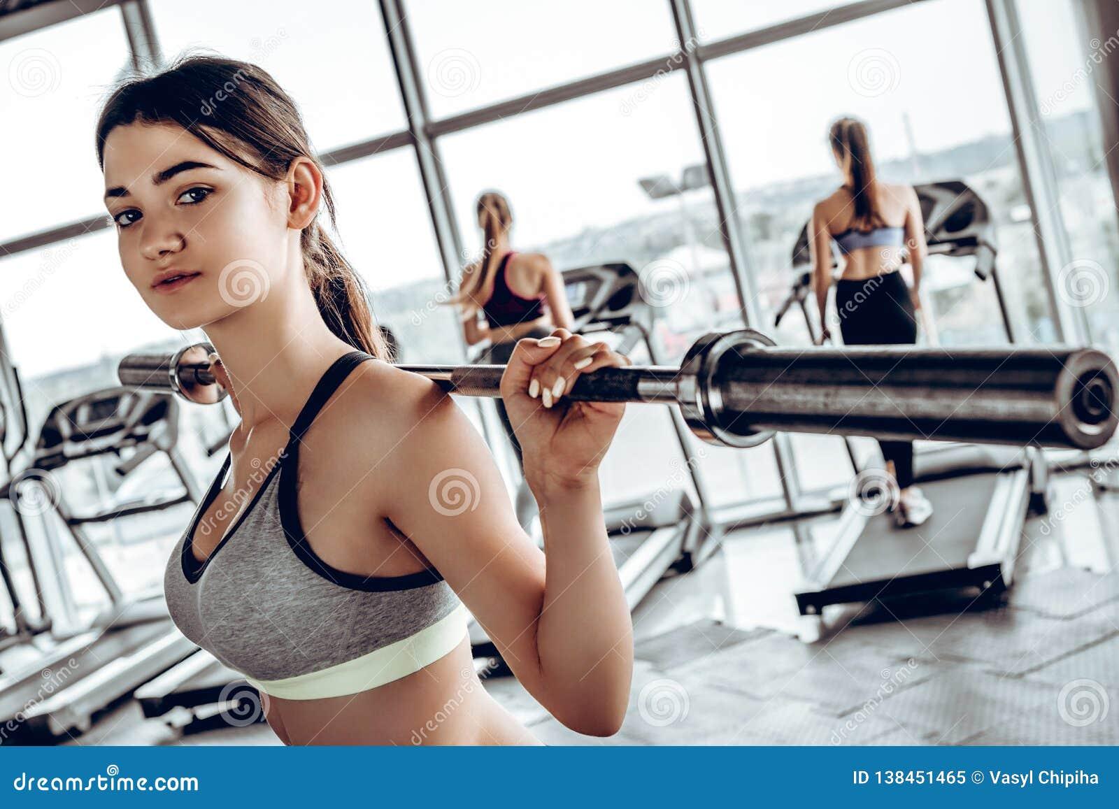 Jovem mulher forte com o corpo atlético bonito que faz exercícios com barbell