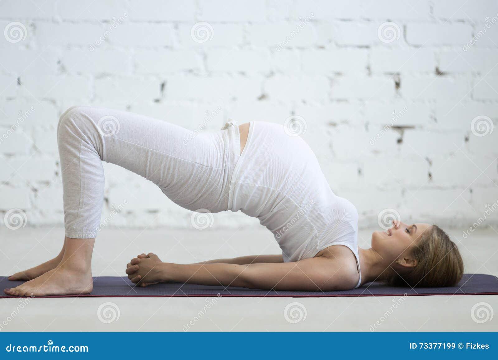 Jovem mulher grávida que faz a ioga pré-natal Pose da ponte