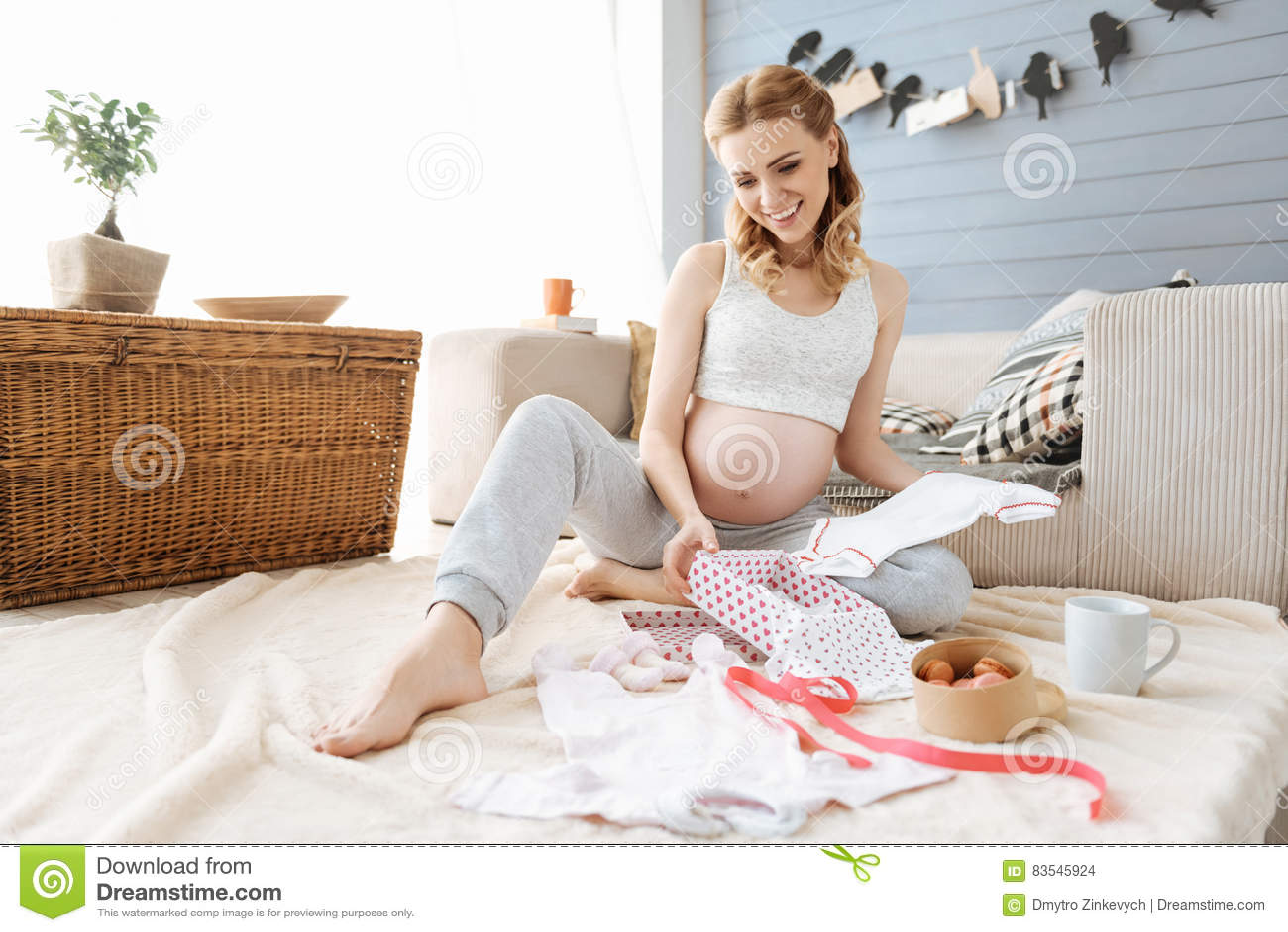 A jovem mulher grávida que sorri felizmente no bebê novo veste-se