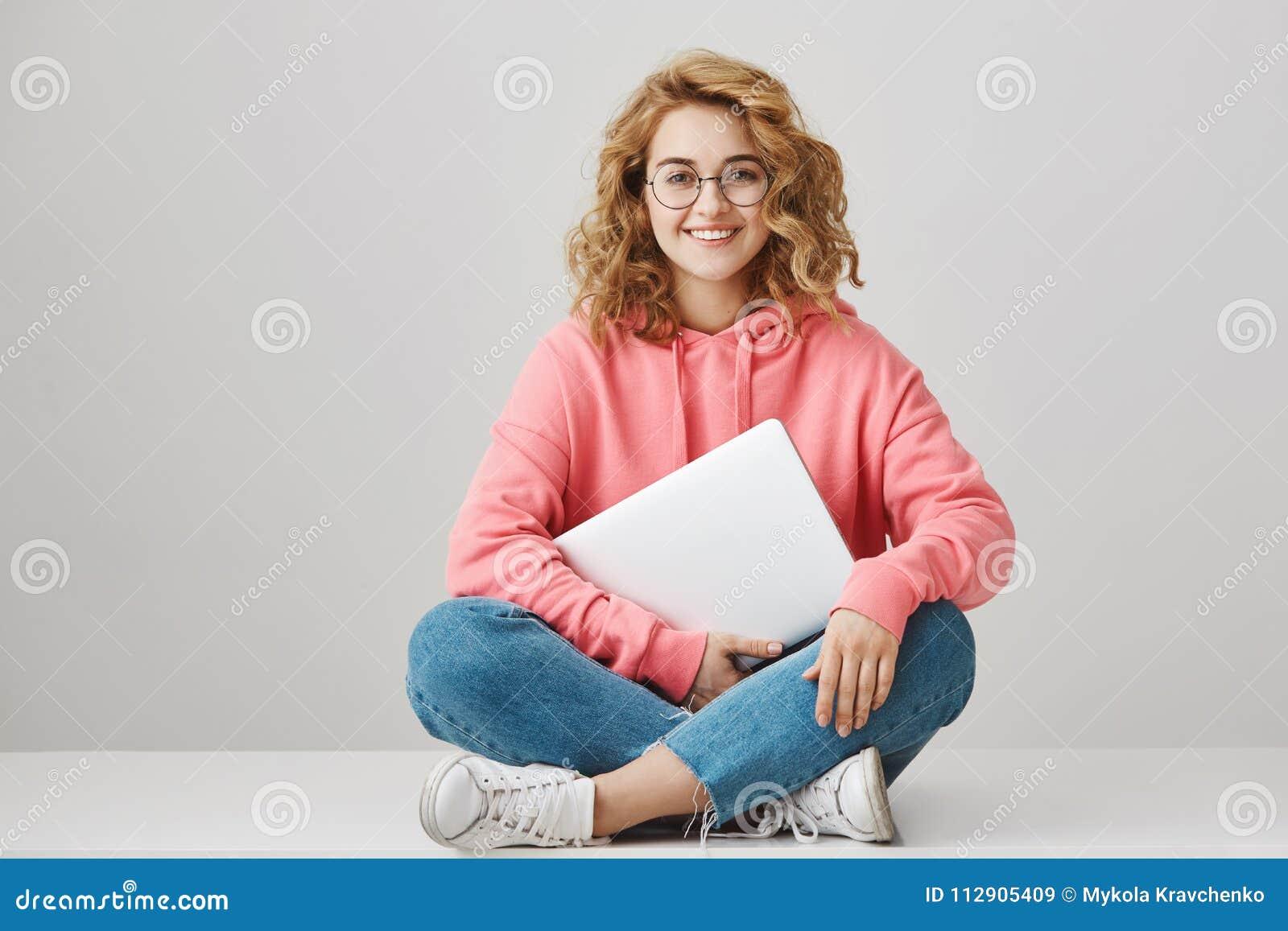 a332e8e80 Jovem mulher inteligente com o cabelo encaracolado que senta-se no assoalho  com pés cruzados