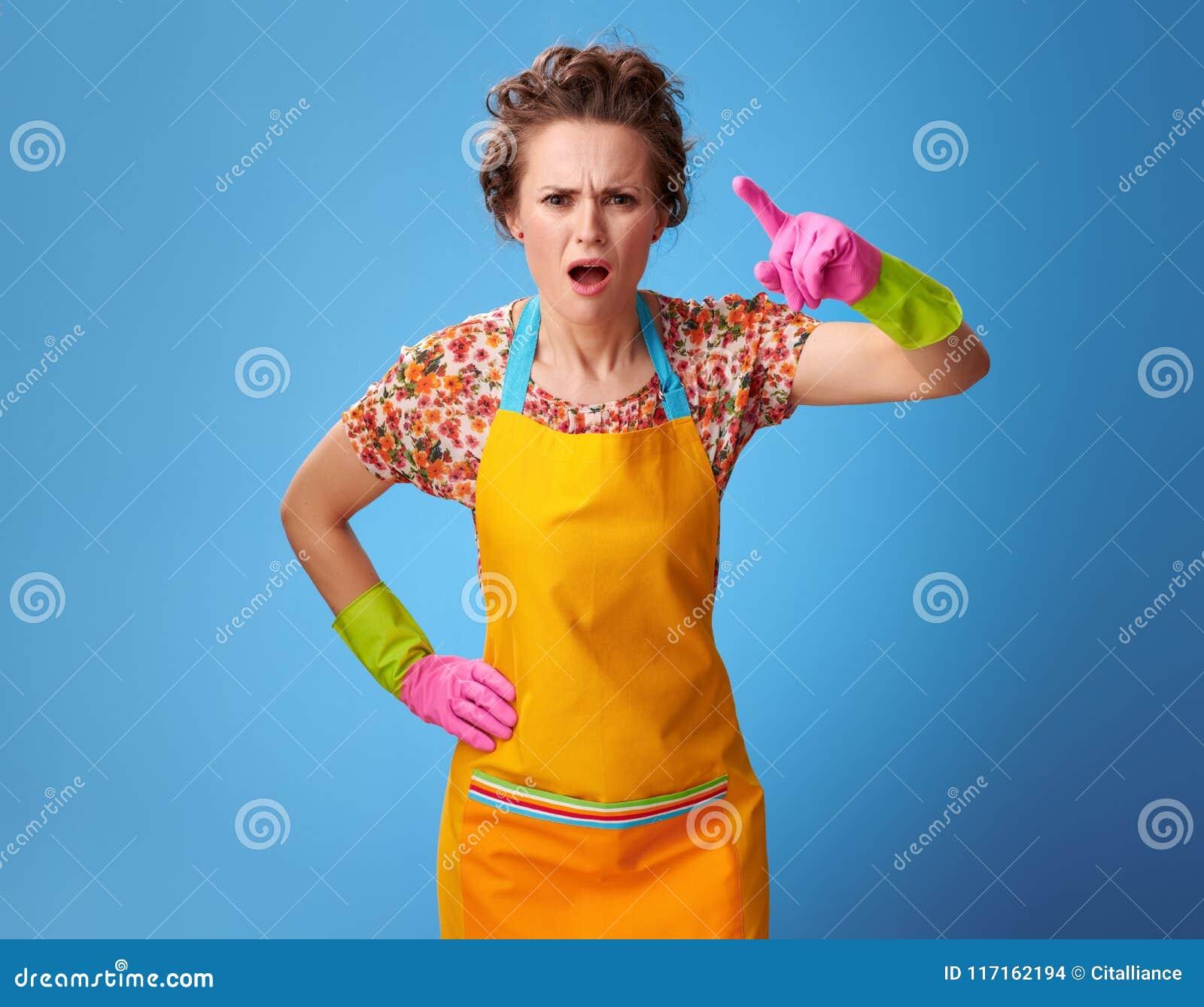 Jovem mulher irritada que ameaça com o dedo no azul