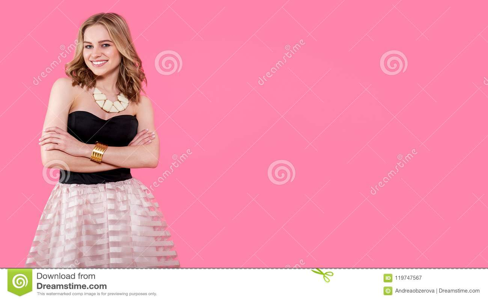 Jovem mulher loura atrativa no vestido de partido elegante e na joia dourada Menina que levanta em um fundo do rosa pastel