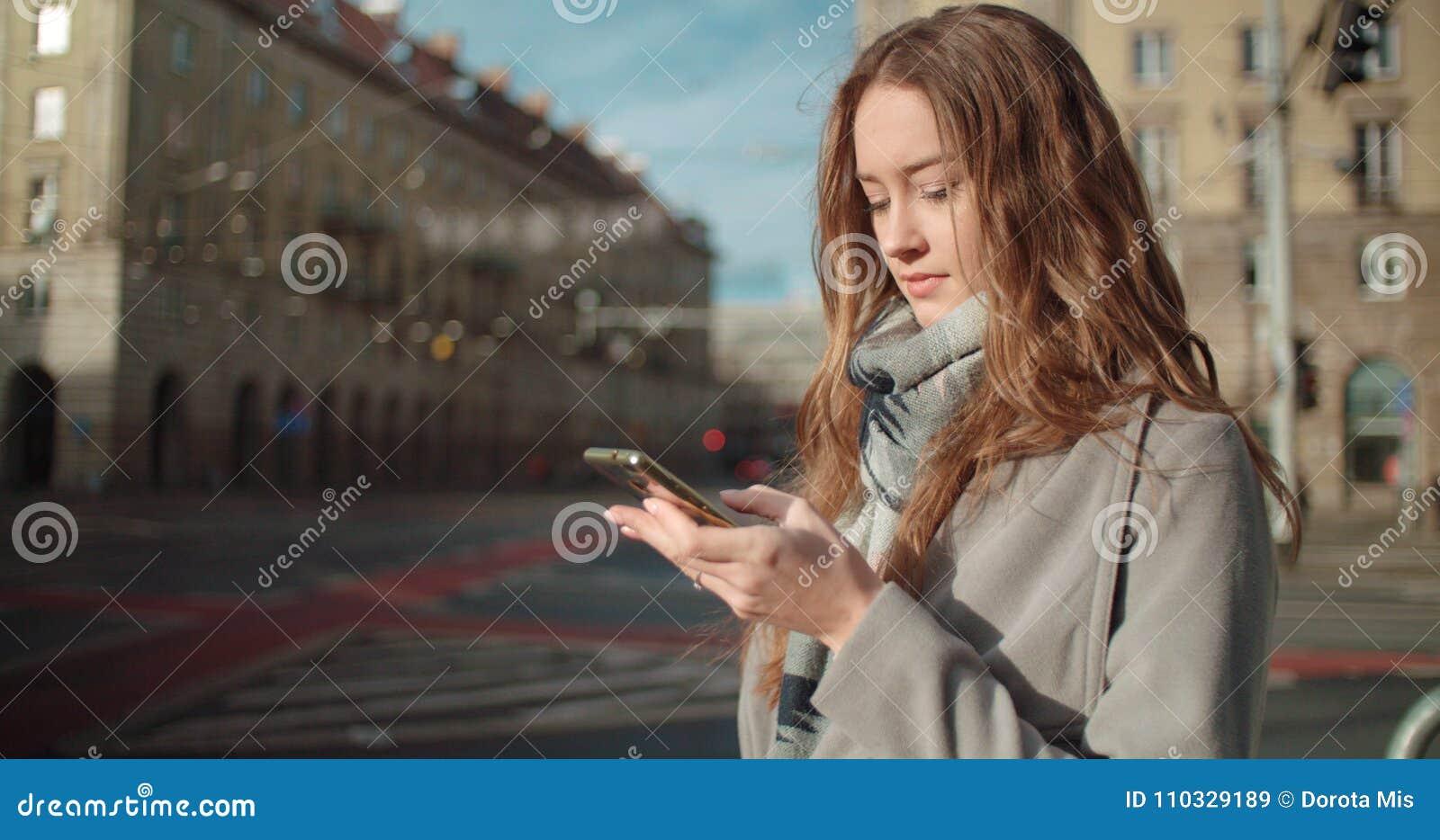 Jovem mulher moreno atrativa que texting no telefone ao estar em uma rua da cidade