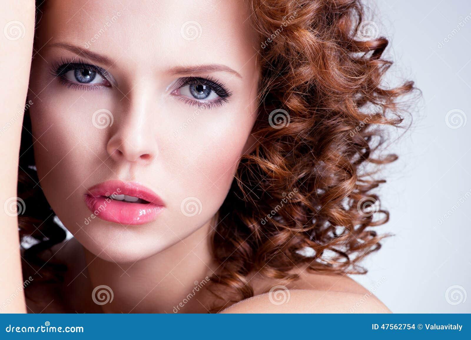 A jovem mulher moreno bonita com brilhante compõe