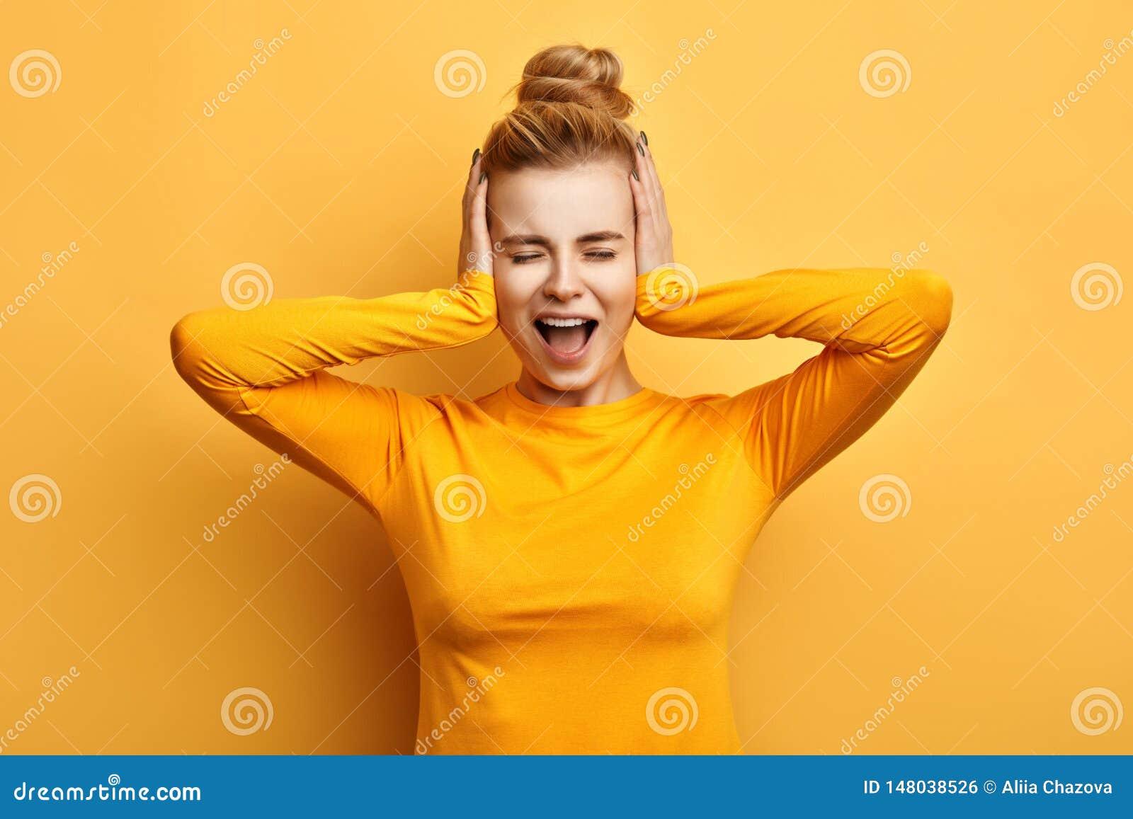 Jovem mulher na camiseta amarela à moda que grita no terror com mãos em suas orelhas