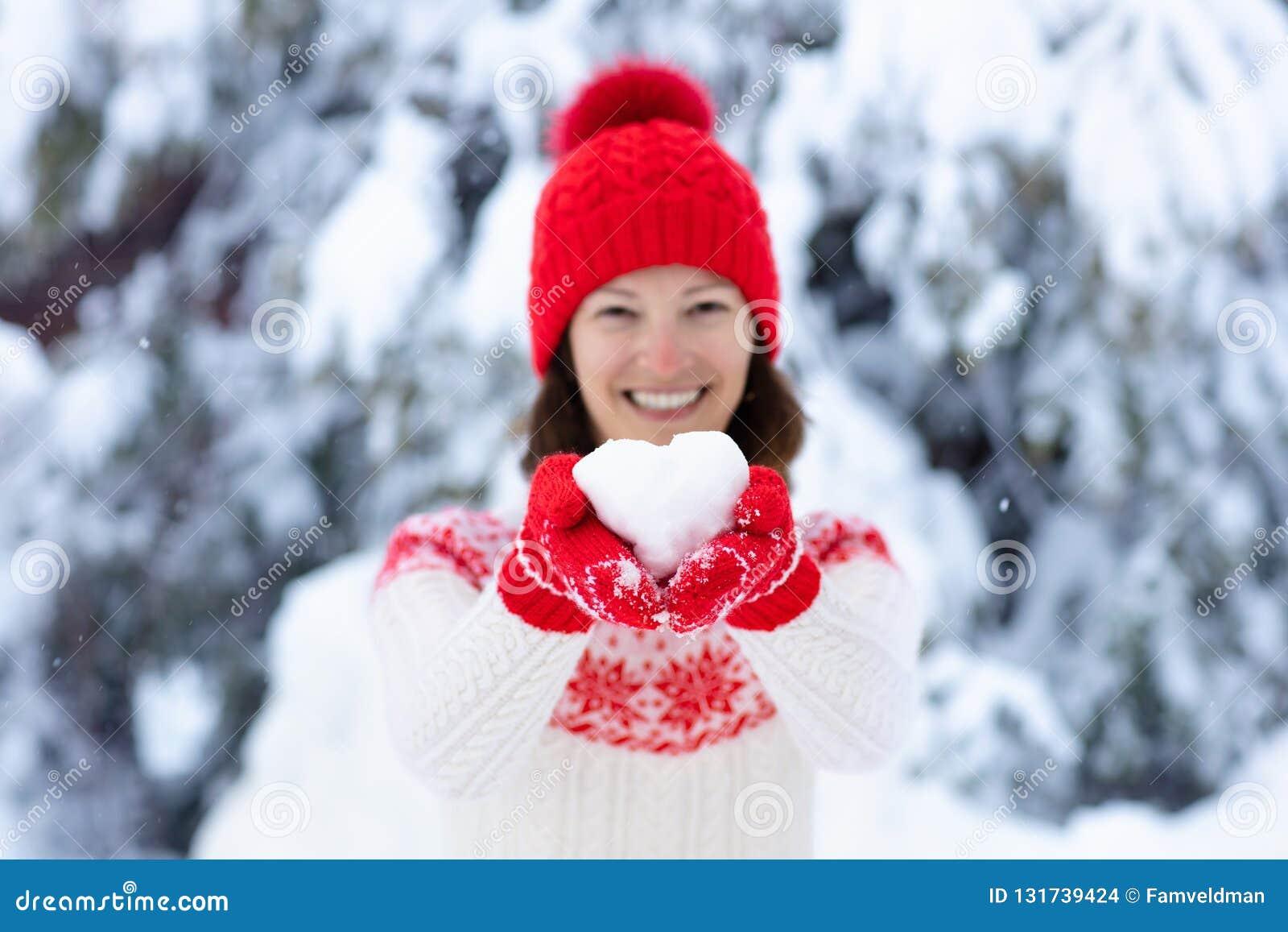Jovem mulher na camiseta feita malha que guarda a bola da neve da forma do coração no inverno Menina no jogo da luta da neve da f