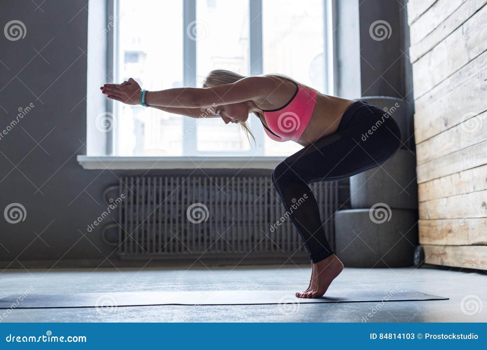 Jovem mulher na classe da ioga, transição do vinyasa à pose
