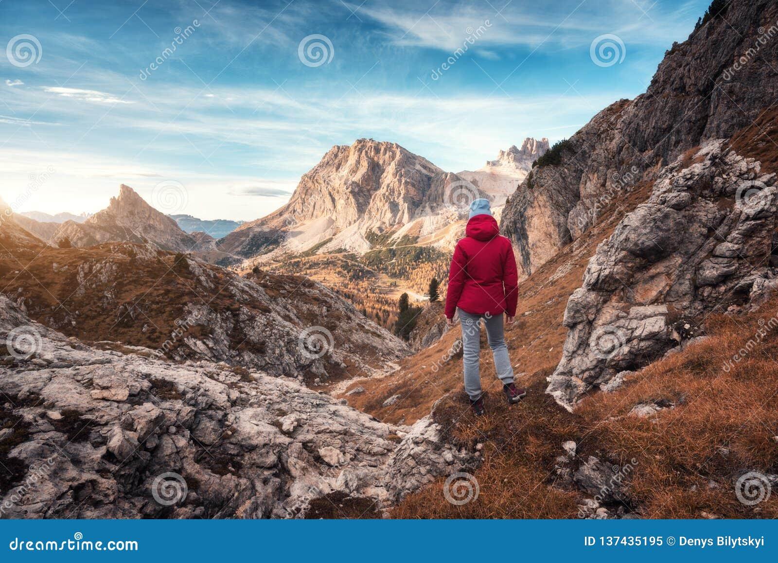Jovem mulher na fuga que olha no pico de montanha alta no por do sol