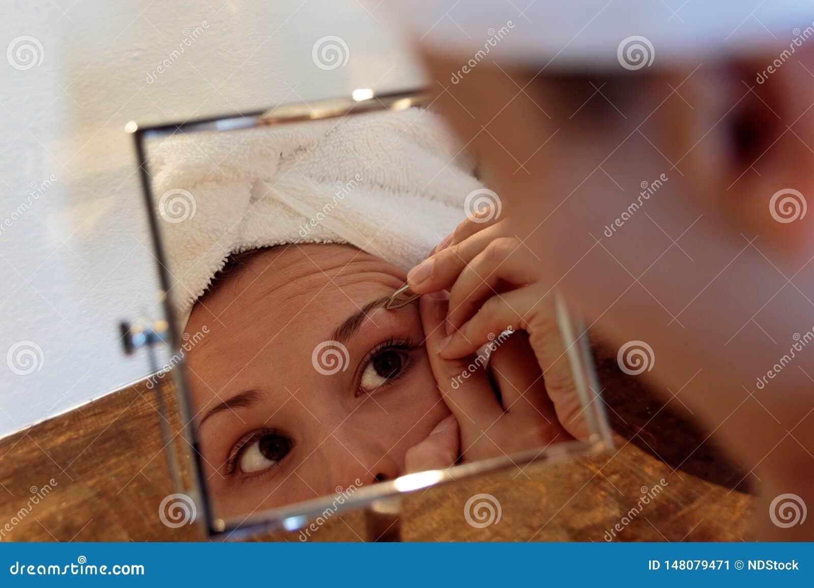 Jovem mulher no banheiro depilação da sobrancelha com pinça