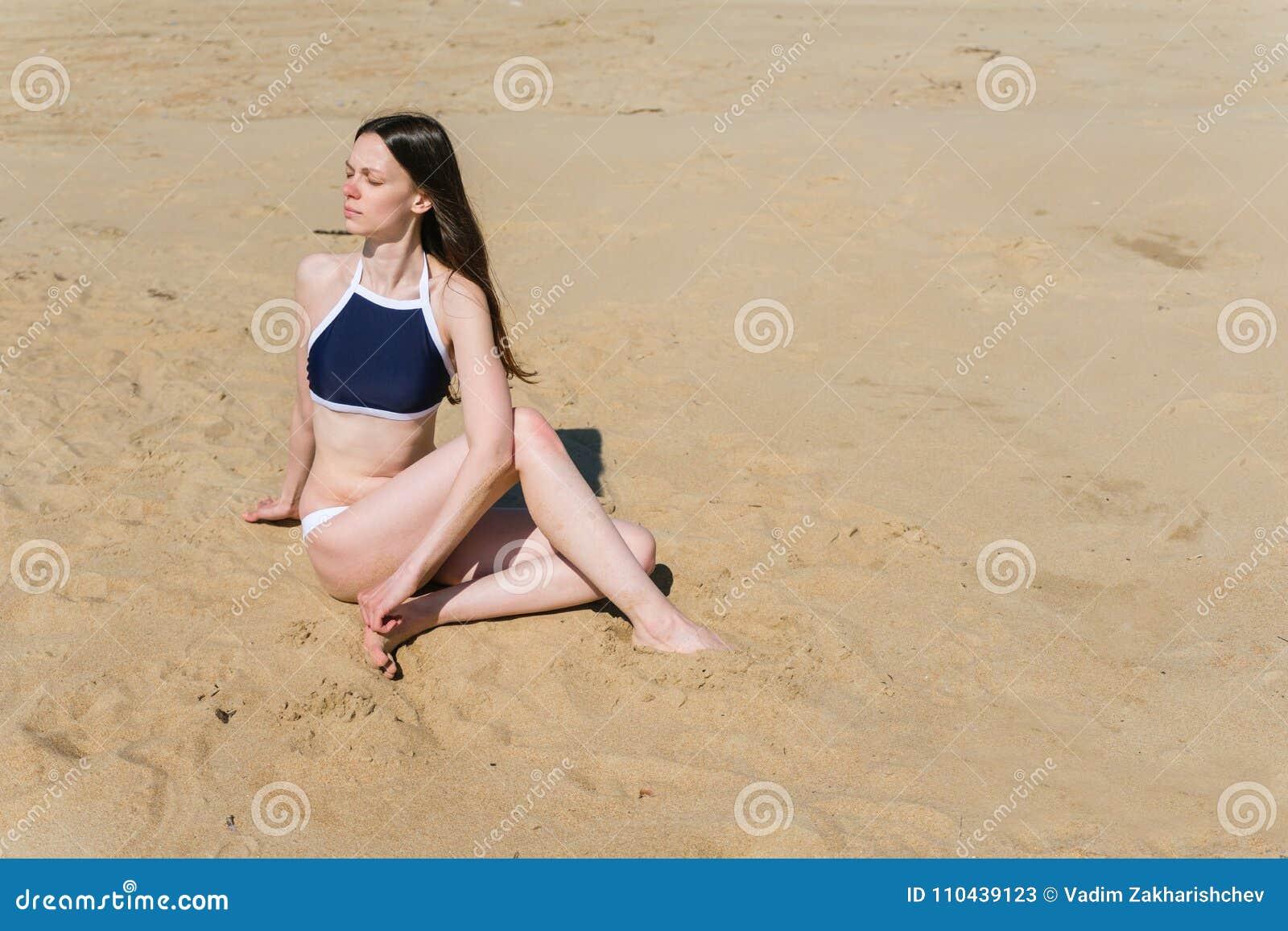A jovem mulher no biquini faz Ardha Matsyendrasana ou meia pose espinal da torção na praia com dunas de areia