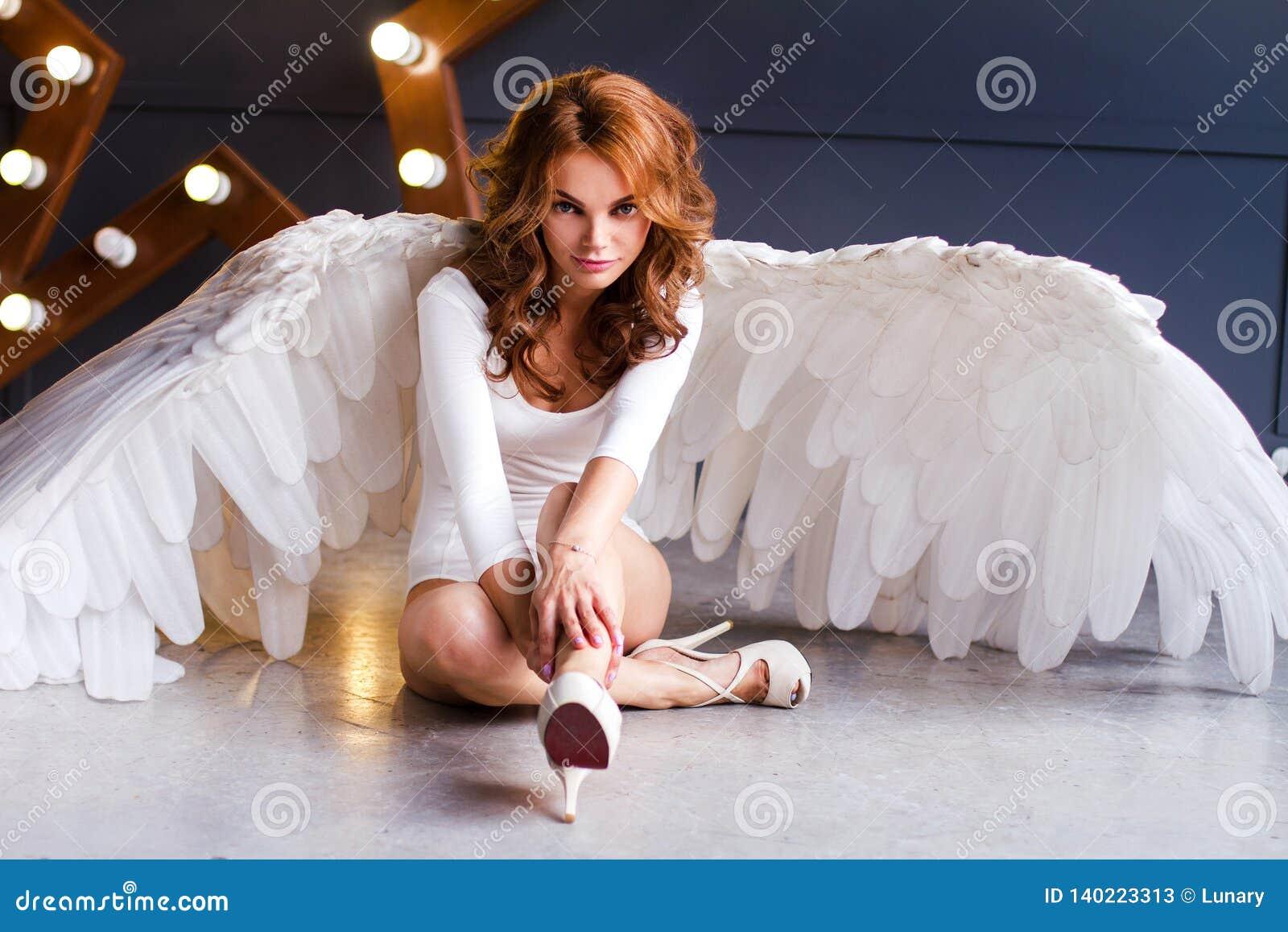Jovem mulher no bodysuit branco com asas do anjo